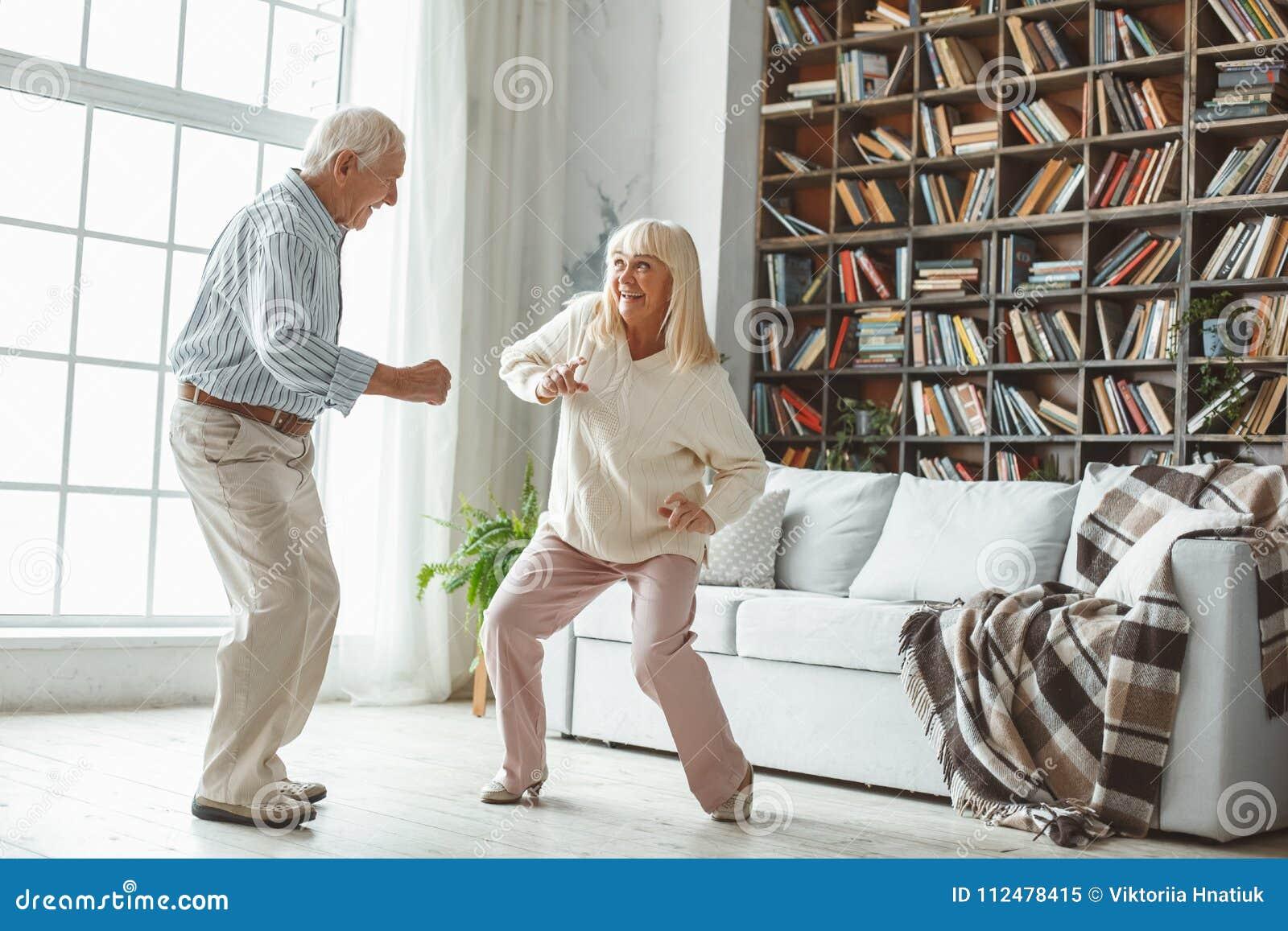 De couples concept supérieur de retraite ensemble à la maison dansant la danse active espiègle