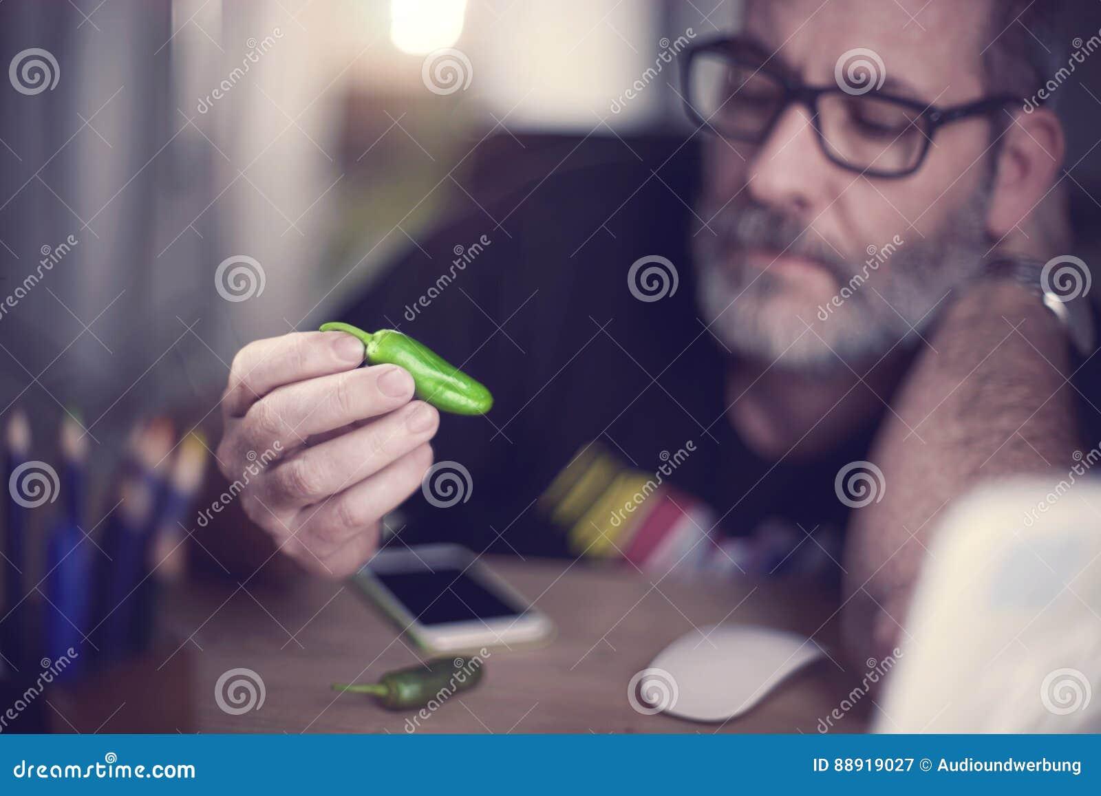 De creatieve ontwerper bekijkt groene paprika, hete Spaanse peperpeper