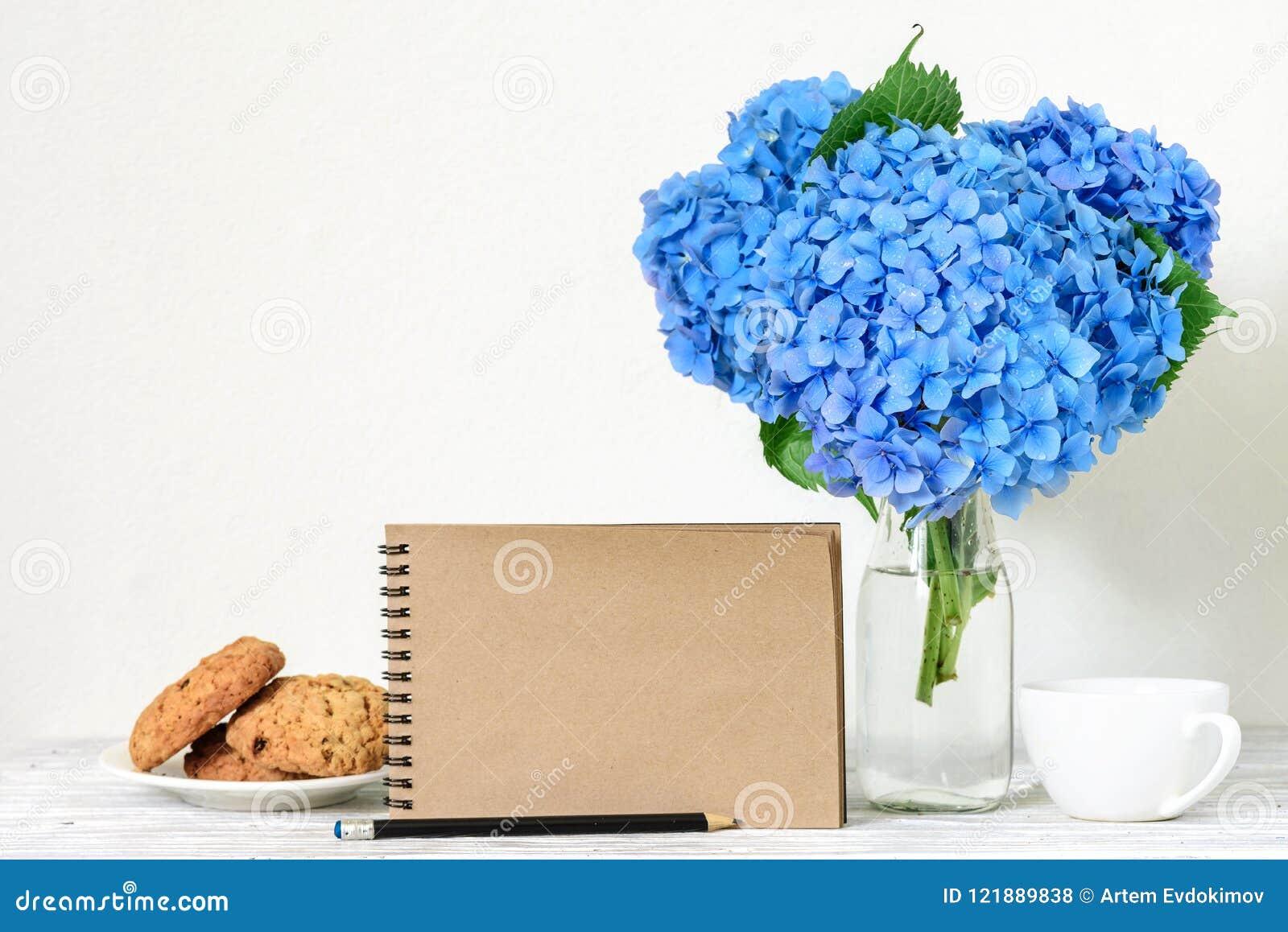 De creatieve spot omhoog met een mooi boeket van blauwe hydrangea hortensia bloeit, koffiekop, haverkoekjes en leeg hipsternotiti