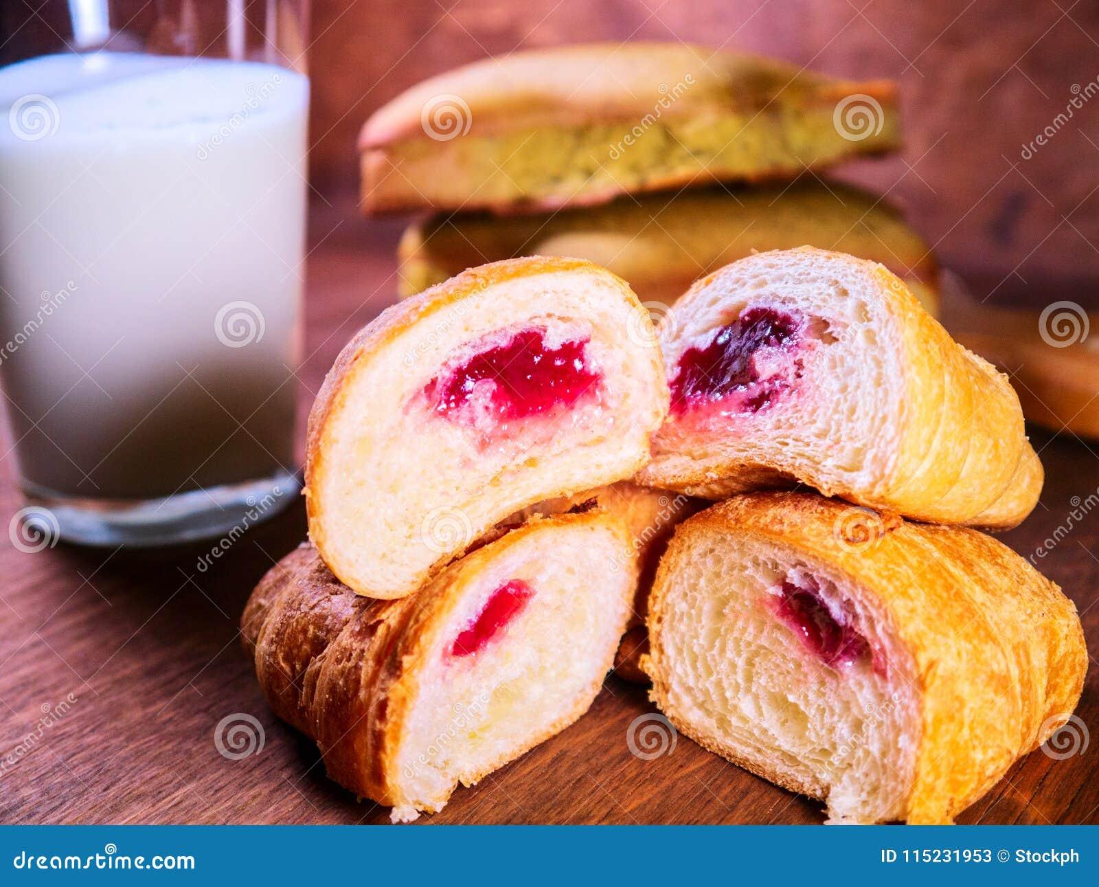 De croissantkers in een besnoeiing ligt bovenop elkaar, naast de cake en de melk