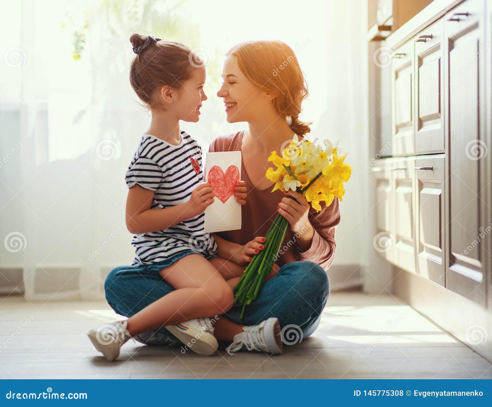 De dag van de gelukkige moeder! de kinddochter geeft moeder een boeket van bloemen aan narcissen en gift