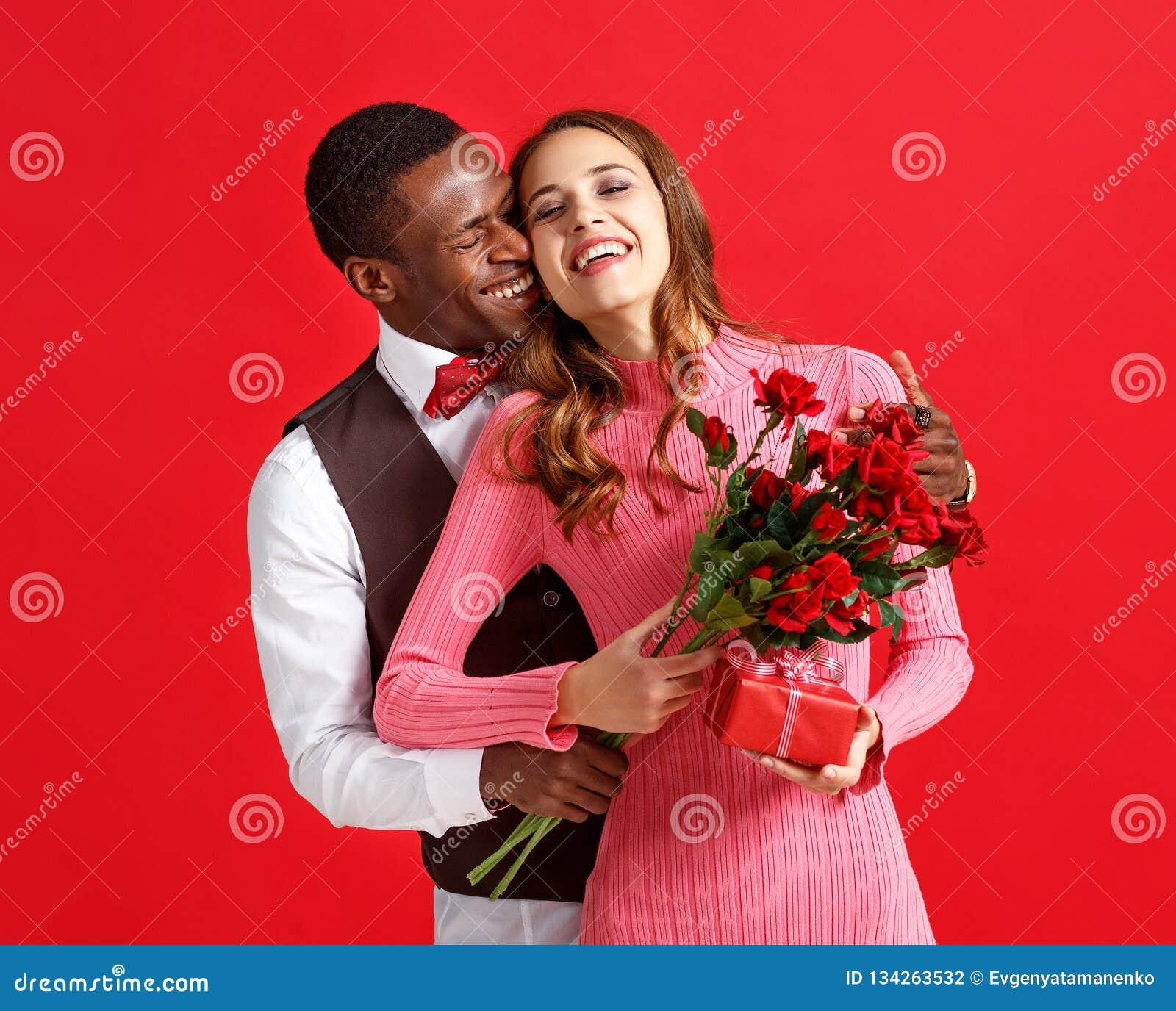 De dagconcept van de valentijnskaart ` s gelukkig jong paar met hart, bloemen, gift op rood