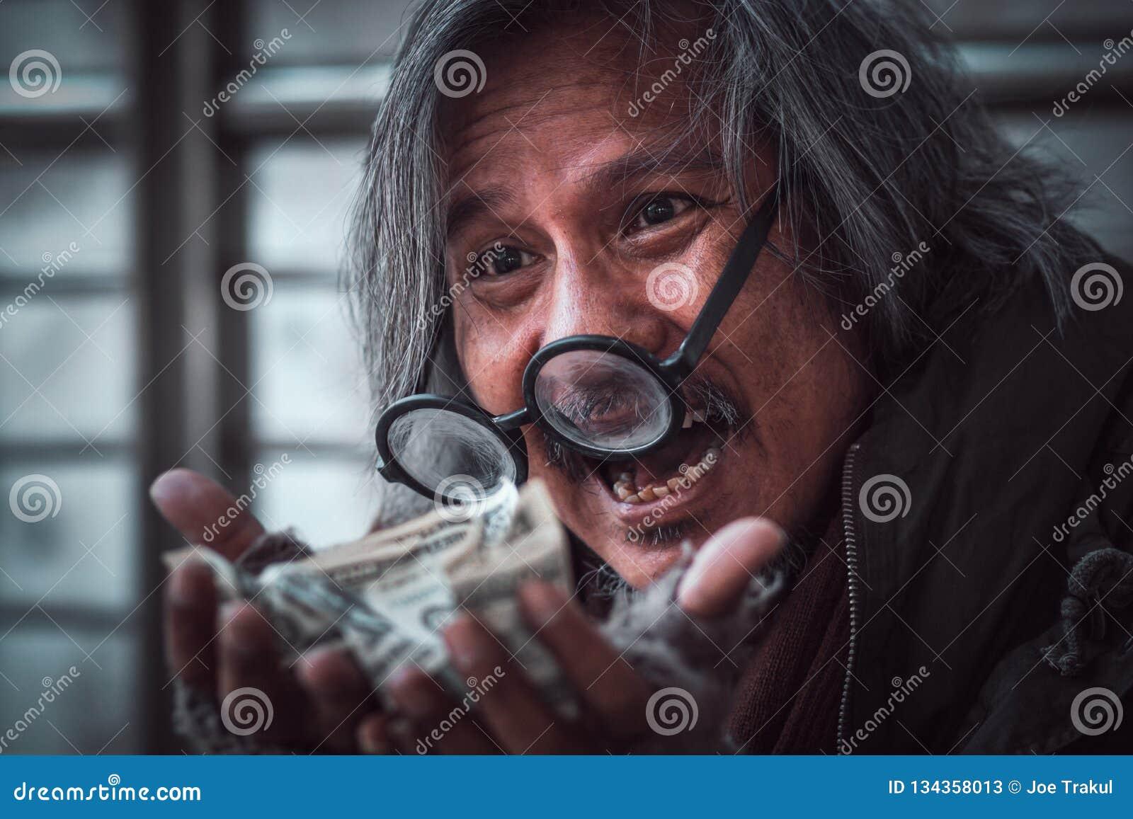 De dakloze mens kreeg heel wat geld op hem handen die gelukkig gezicht met glimlach maken - omhoog sluiten