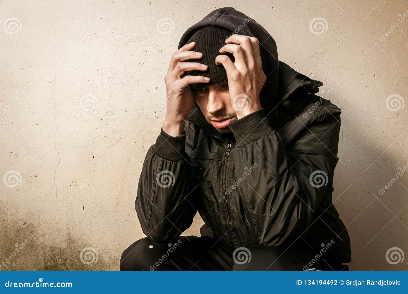 De dakloze de mensendrug en alcohol wijden zitting alleen en gedeprimeerd op de straat die bezorgd en eenzaam op de koude de wint