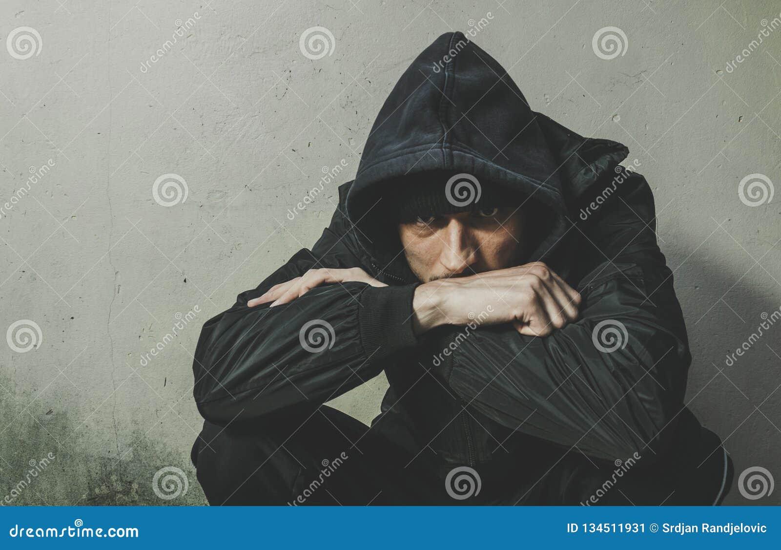 De dakloze van de mensendrug en alcohol verslaafdenzitting alleen en gedeprimeerd op de straat in de winter kleedt het voelen van