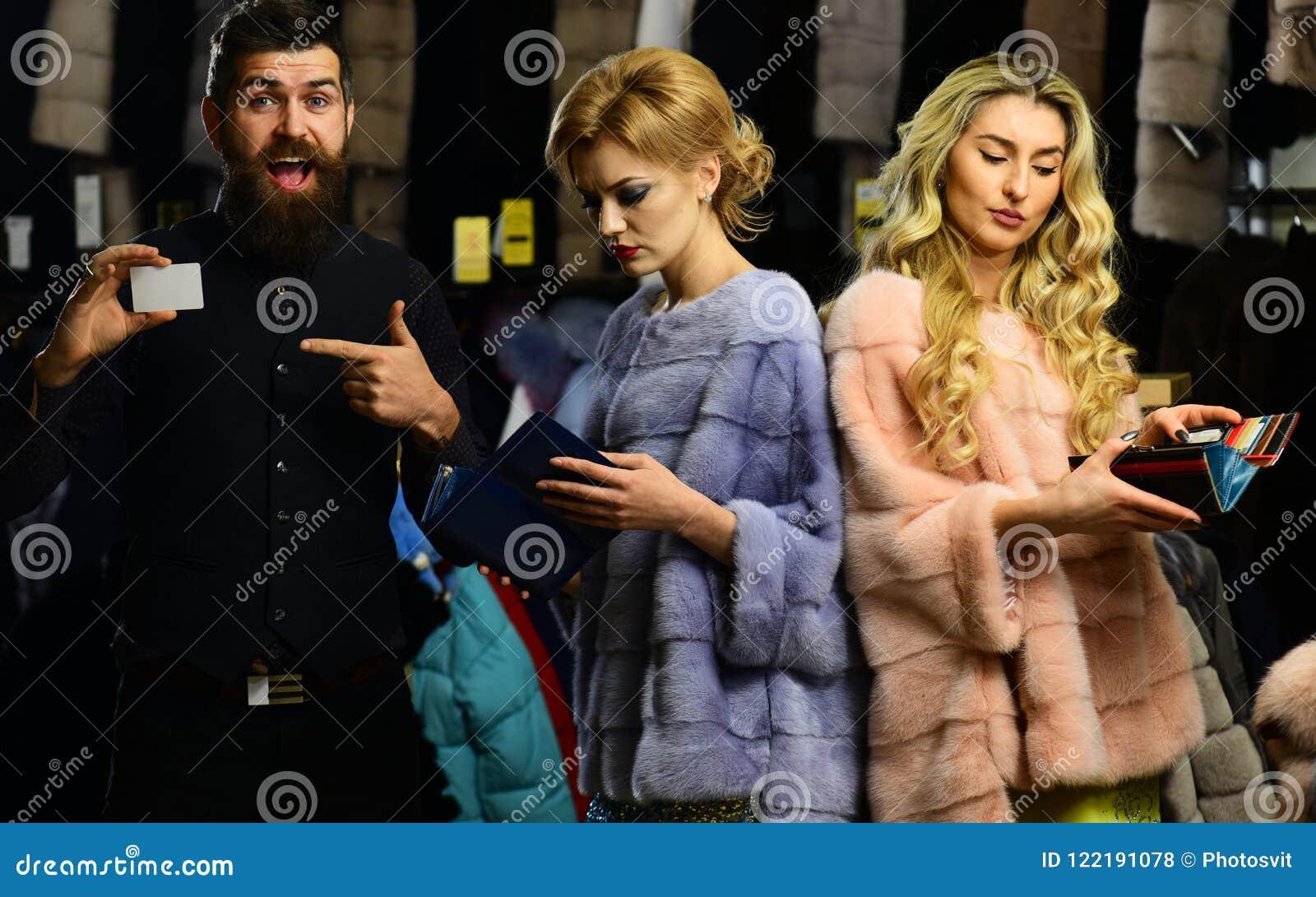 De dames en de heer kopen overjassen Kerel met baard en vrouwen