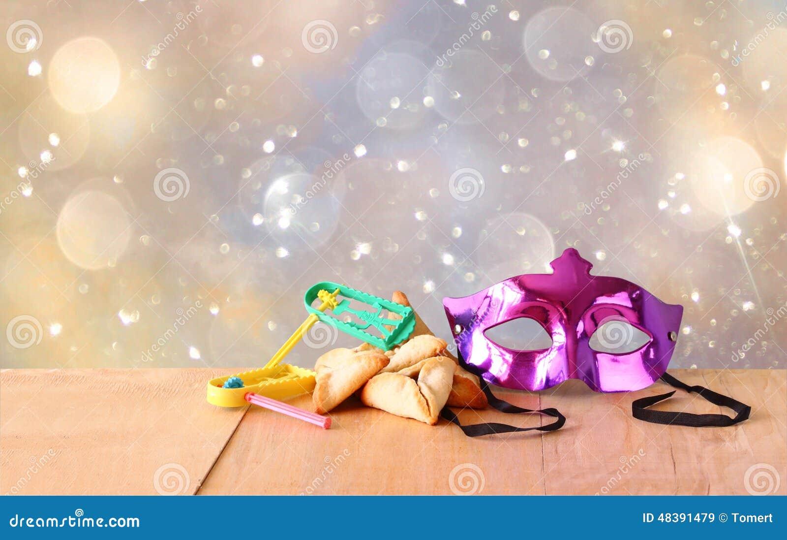 De de Hamantaschenkoekjes of hamans oren, noisemaker en het masker voor Purim-viering (Joodse vakantie) en schitteren achtergrond