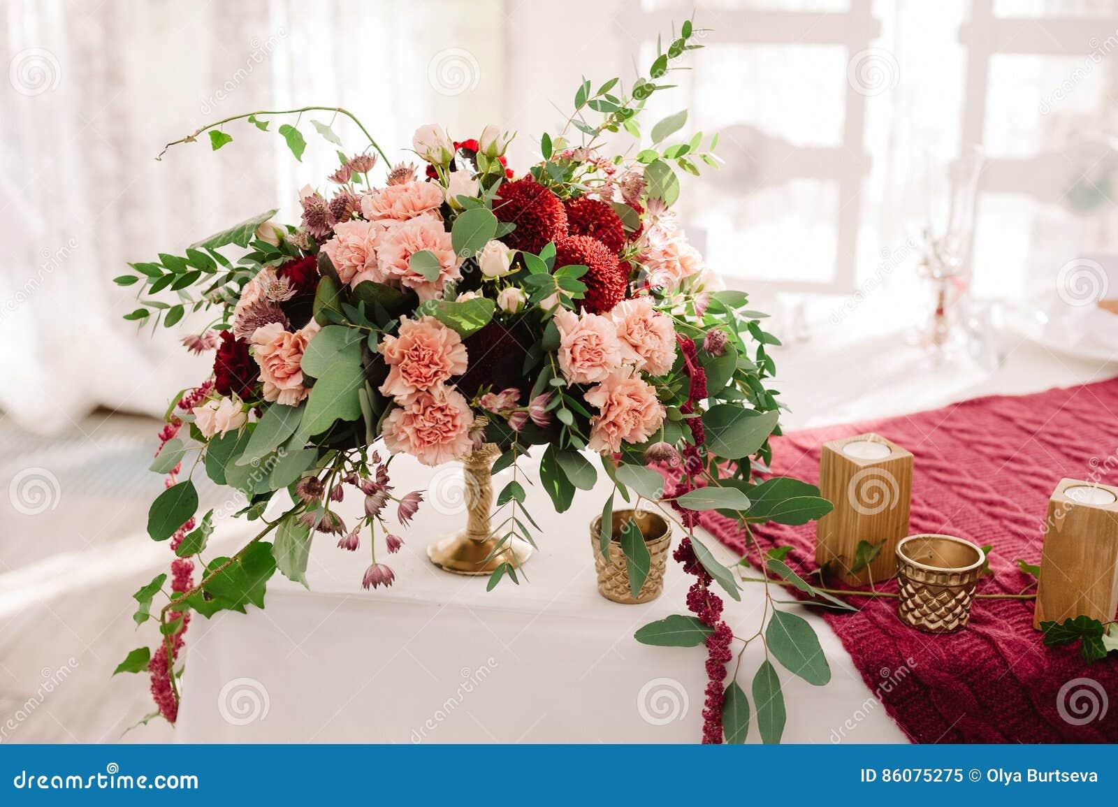 De decoratie van de huwelijkslijst met de rode en roze bloemen op de witte doek