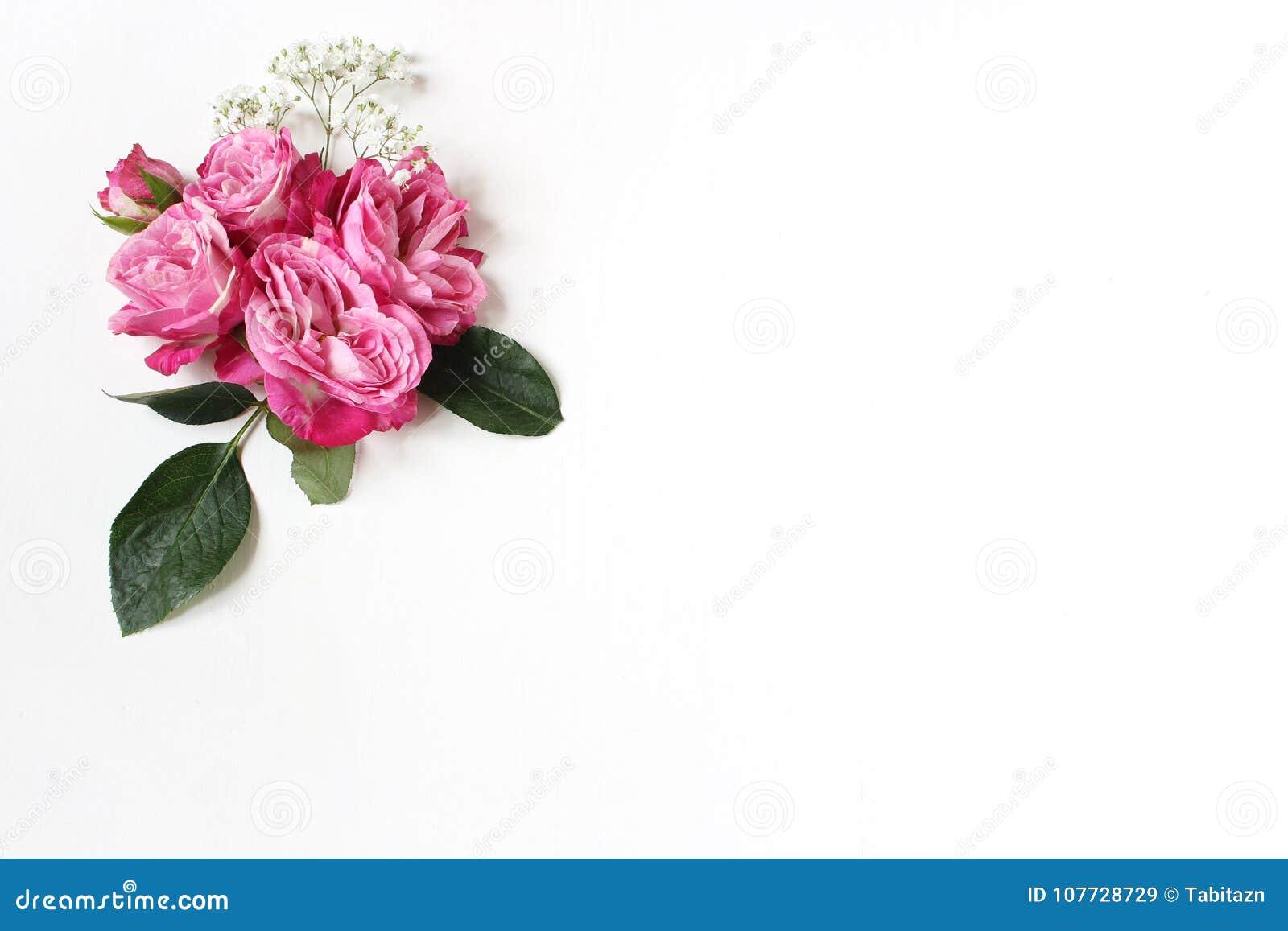 De decoratieve bloemensamenstelling met roze rozen, groene bladeren en en baby` s adem Gypsophila bloeit op witte lijst