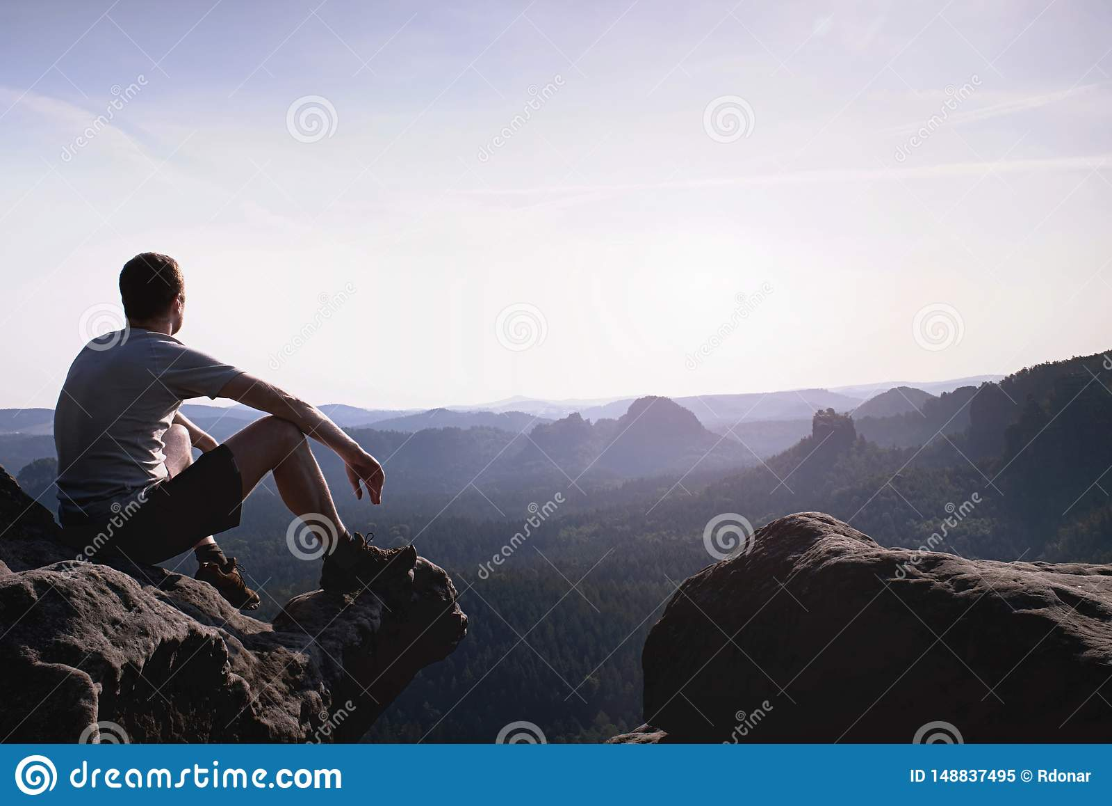 De denkende mens zit op rots Mens bij het blootgestelde top letten op