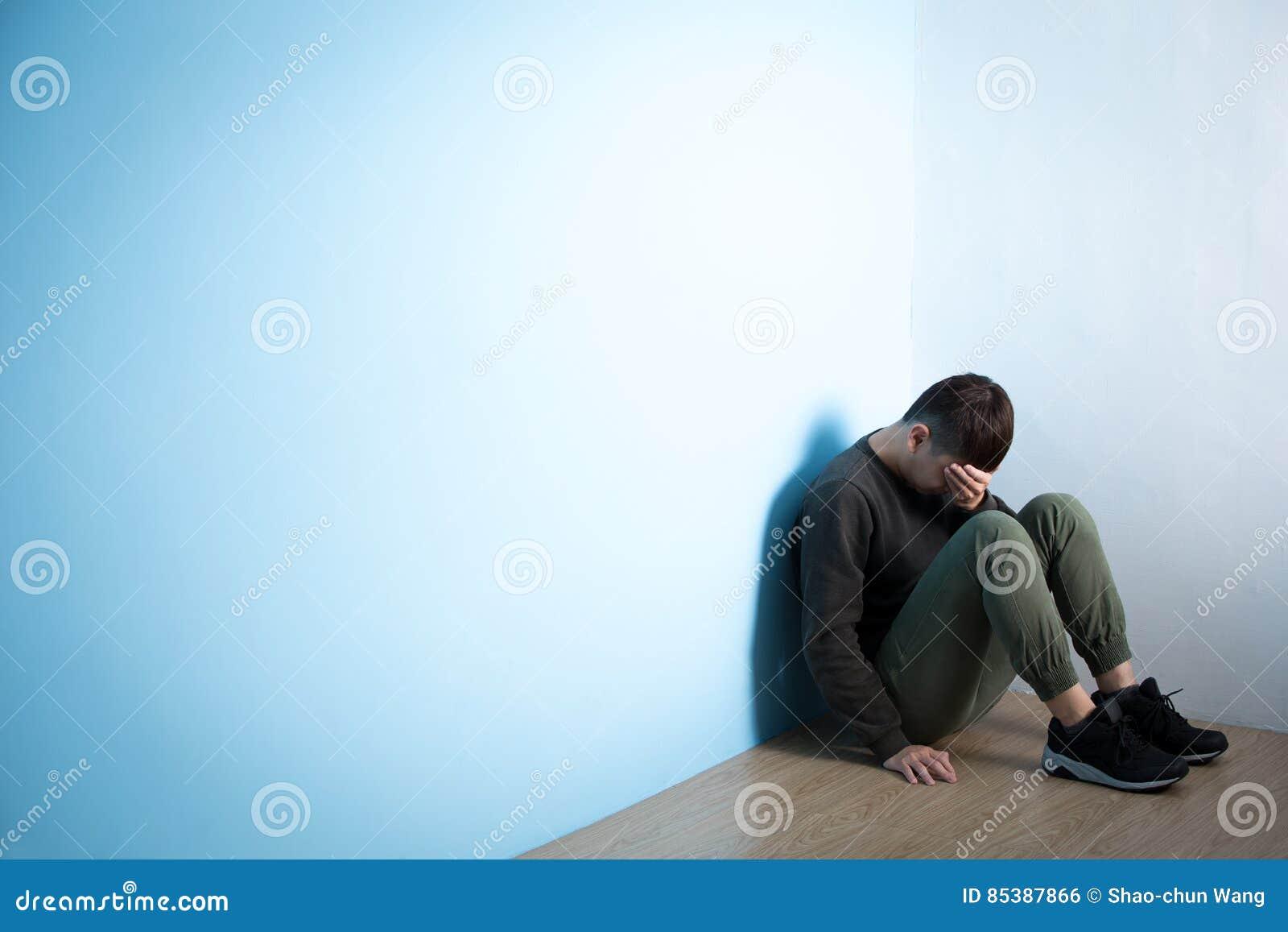 De depressiemens zit op vloer