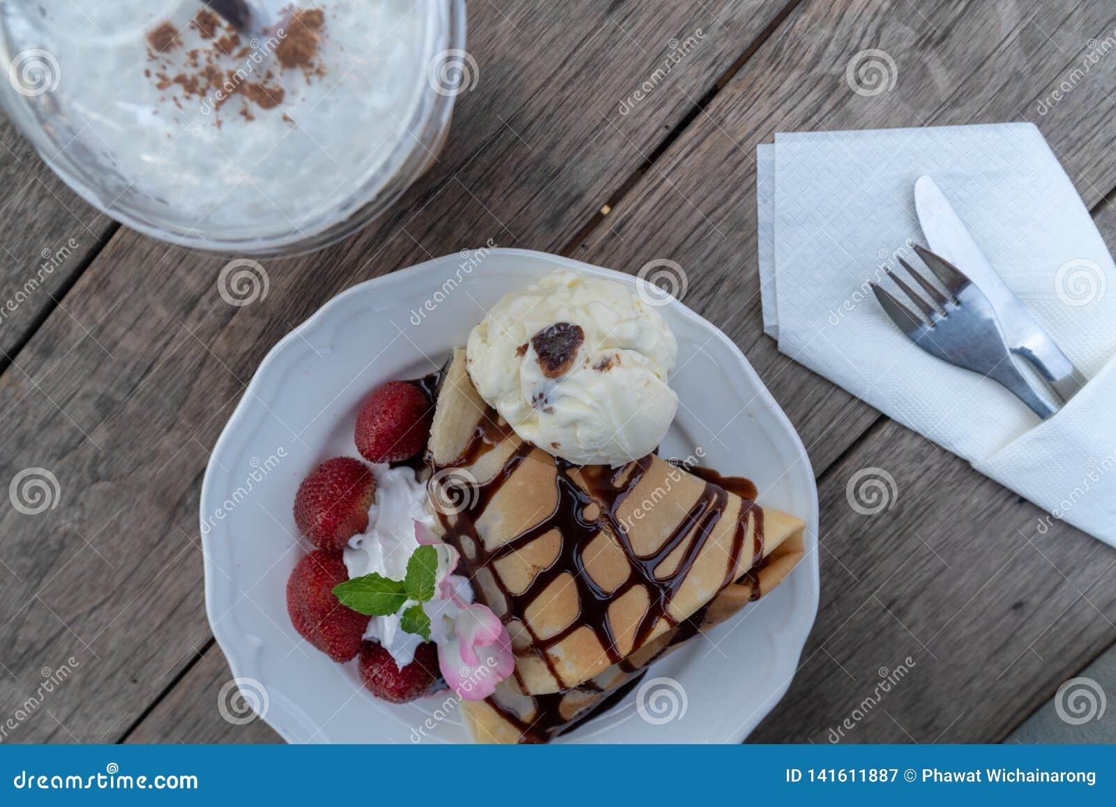 De dessertplaat van omfloerst met aardbei, banaan, en roomijs op houten lijst