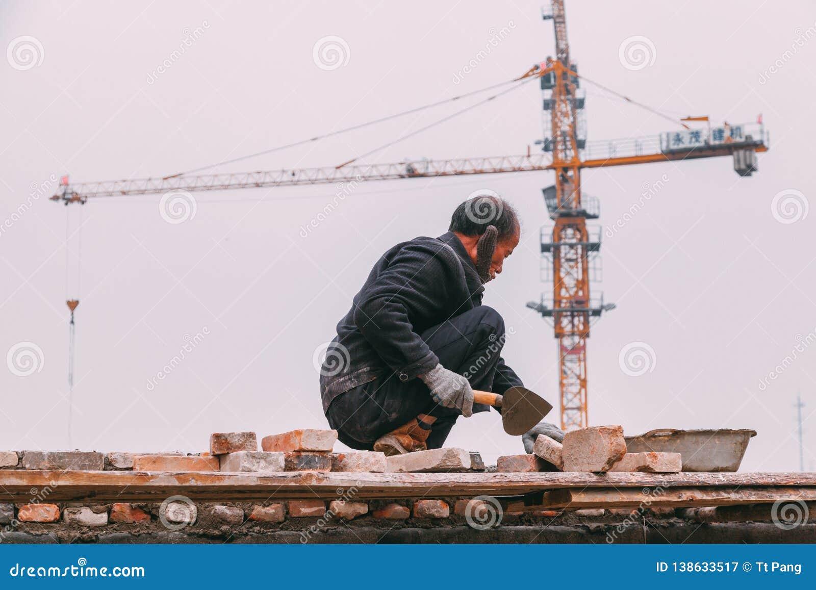 18 de dezembro de 2014 Pequim homens em um canteiro de obras na cidade com guindastes, tijolos takeing