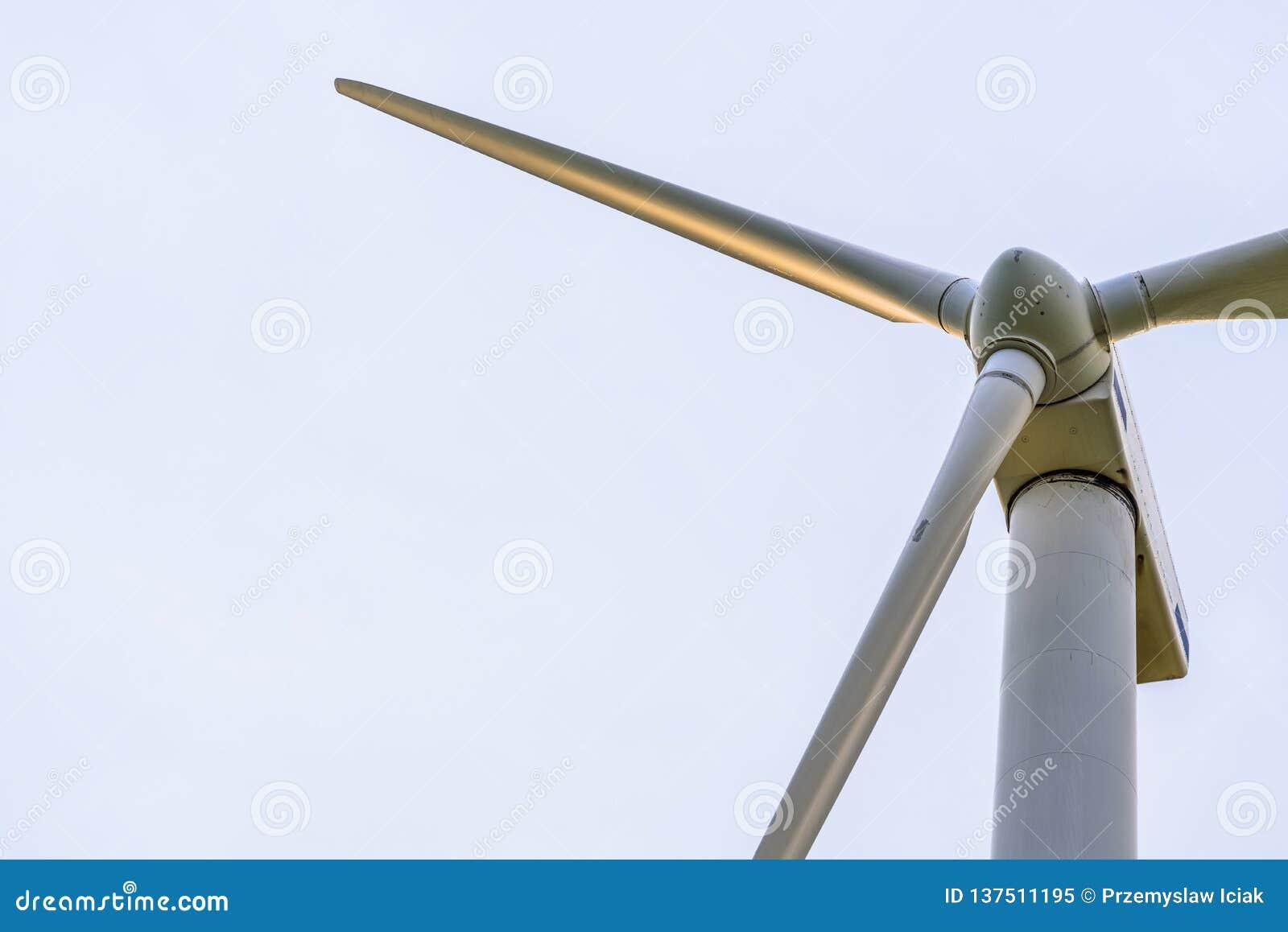De dichte omhooggaande mening van de windturbine over een blauwe hemel