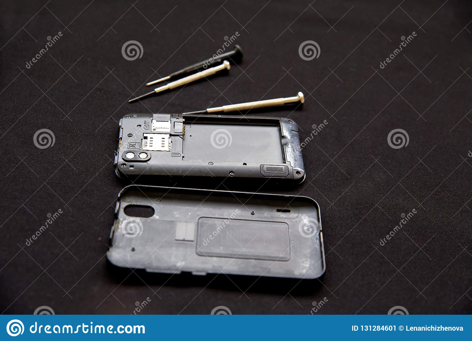 De dienst van de elektronikareparatie - de technicus bevestigt gebroken celtelefoon