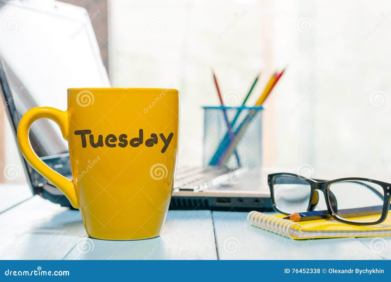 De dinsdag op gele koffie of theekop bij houten raad wordt geschreven dient, werkplaats, de ochtendachtergrond die van het bureau