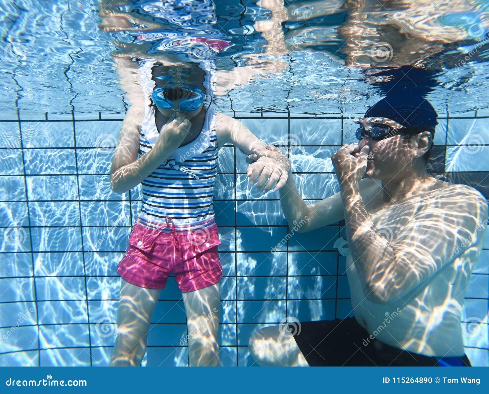De dochter die van het vaderonderwijs in zwembad ademen