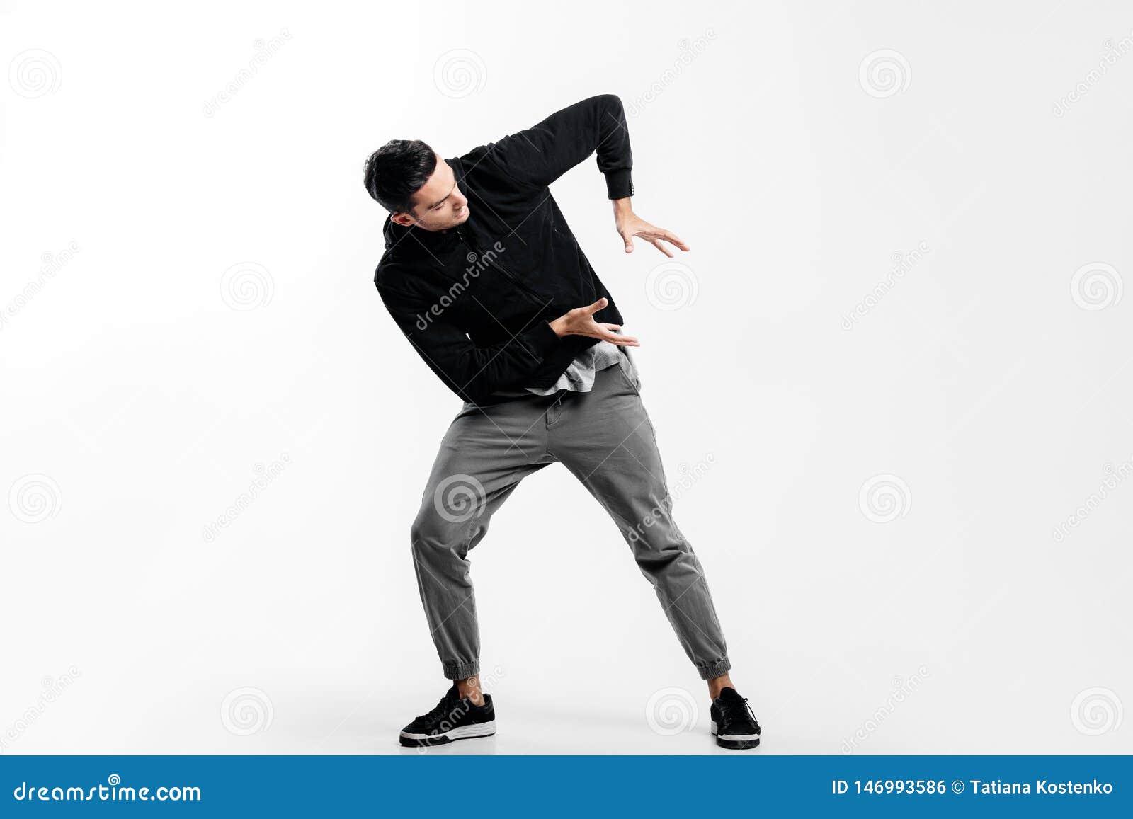 De donker-haired jonge mens die een zwart sweatshirt en een grijze broek dragen is het dansen straatdans Hij maakt gestileerde be