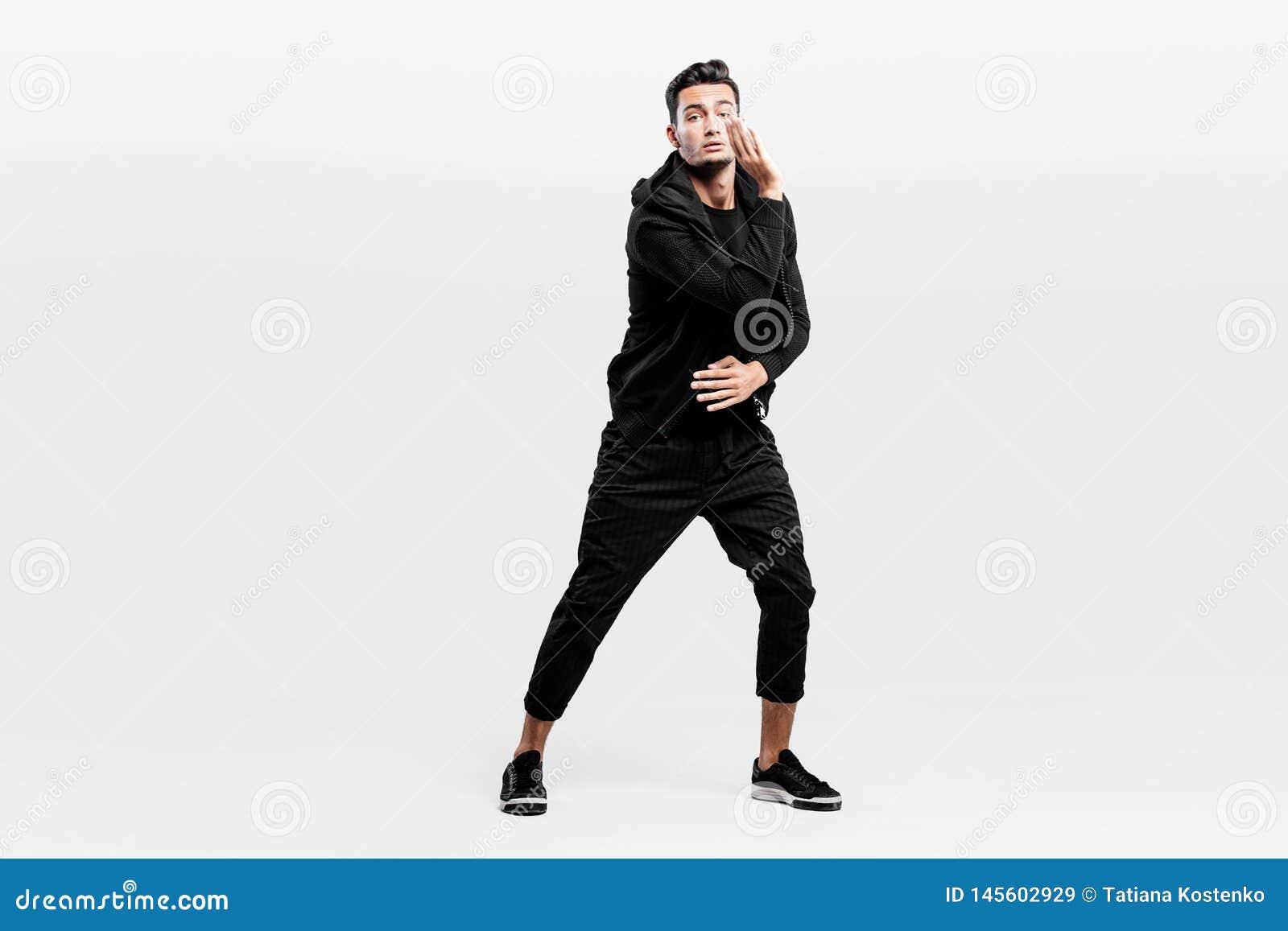De donker-haired modieuze jonge mens gekleed in modieuze zwarte kleren is het dansen straatdansen Hij maakt gestileerde beweginge