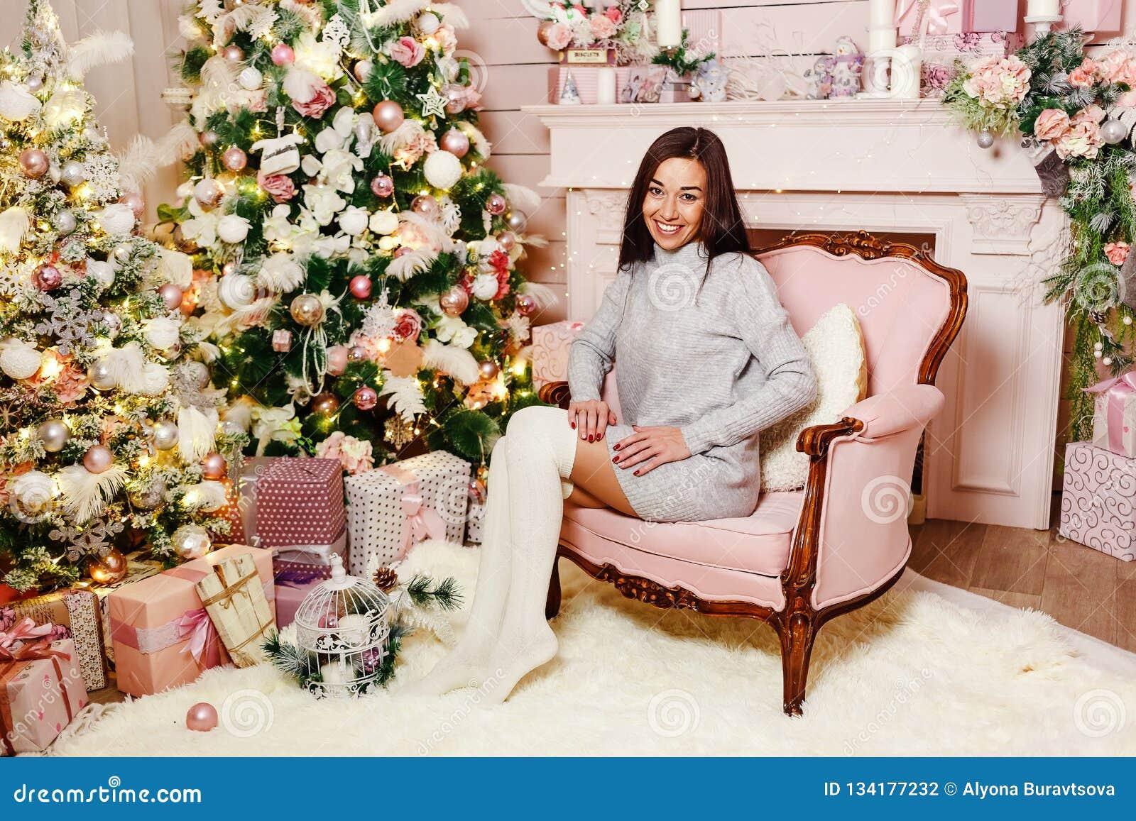 De donkerbruine jonge vrouw zit als voorzitter dichtbij een Kerstboom