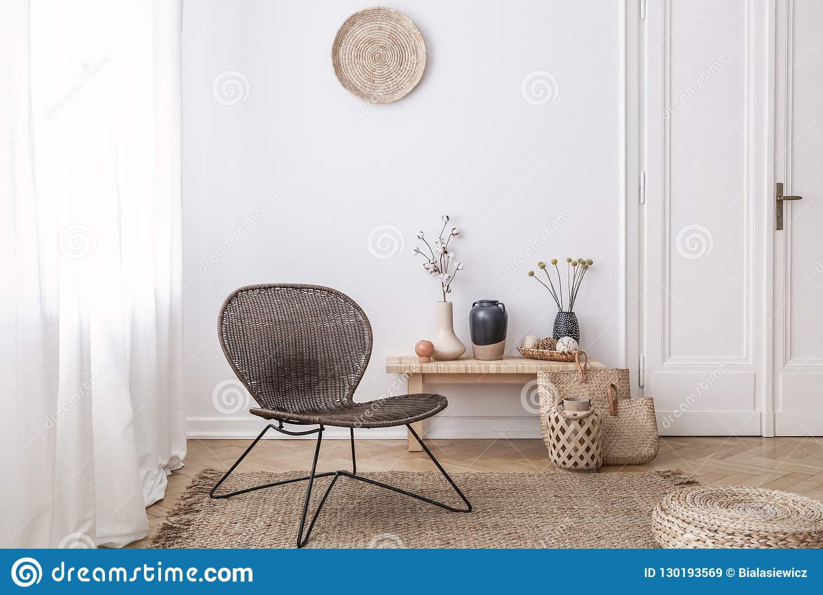 De donkere, moderne rieten stoel in een wit woonkamerbinnenland met een houten bank en de decoratie maakten van natuurlijke mater