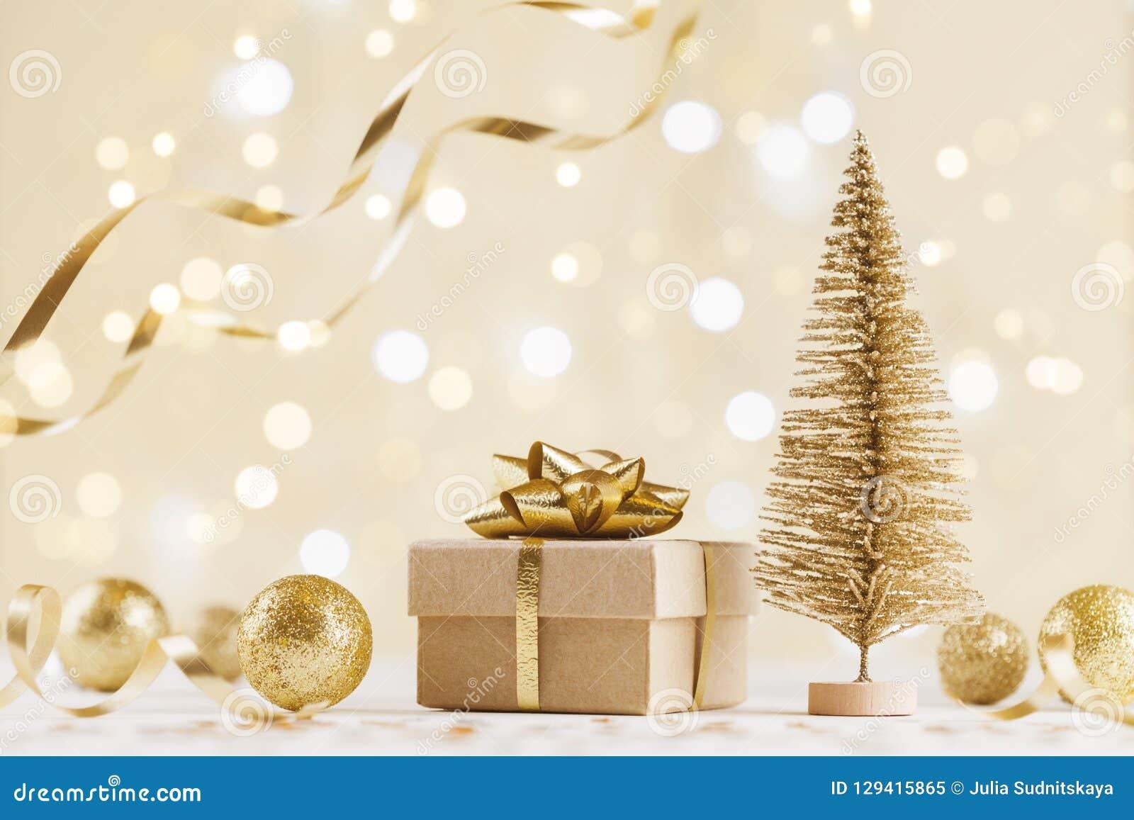 De doos van de Kerstmisgift tegen gouden bokehachtergrond De groetkaart van de vakantie
