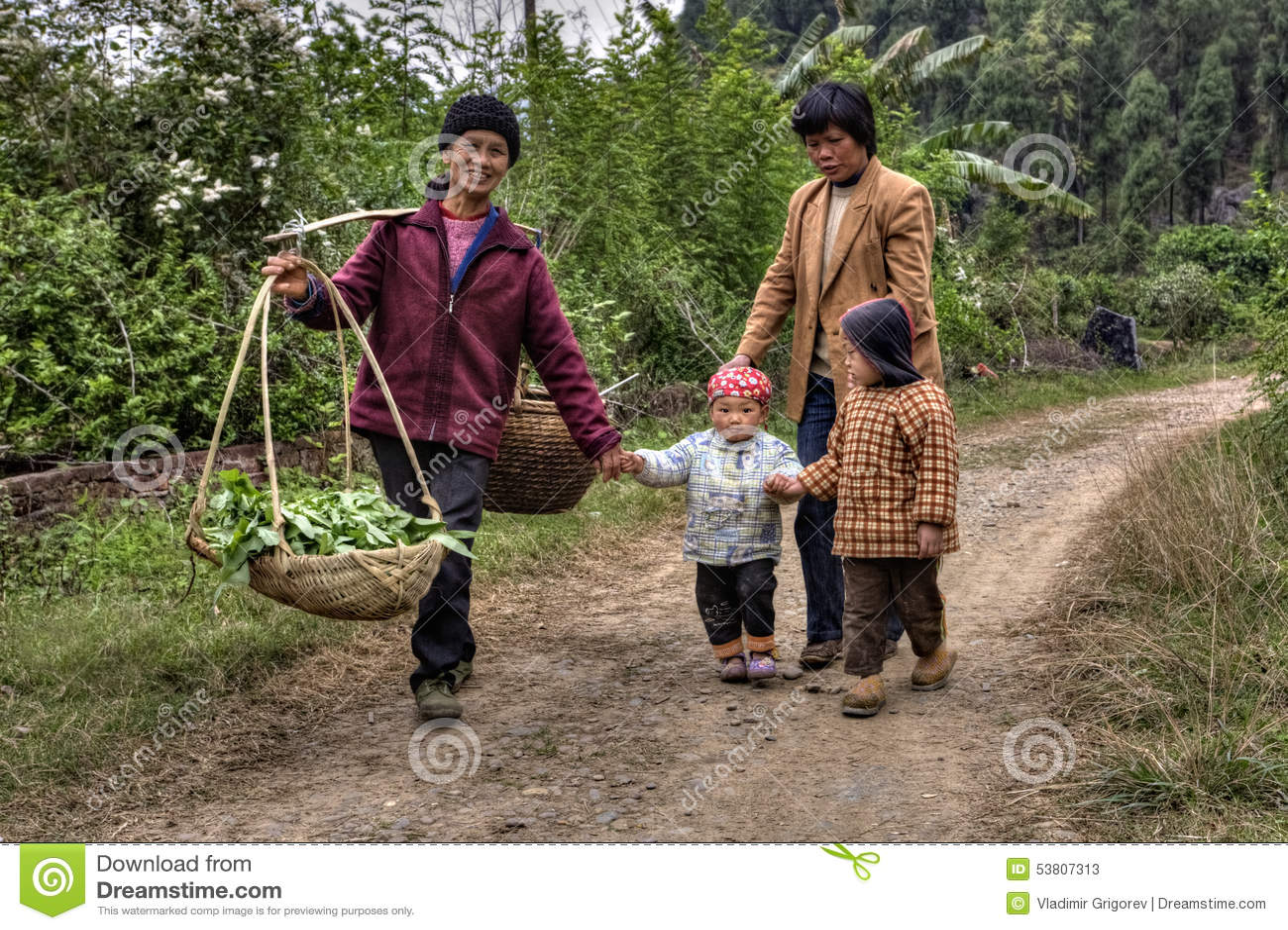 De dorpsbewoners in China, vrouwen met kinderen, zijn bij de landweg