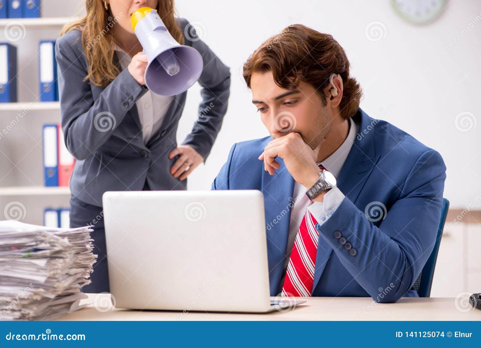 De dove werknemer die gehoorapparaat gebruiken die aan werkgever spreken
