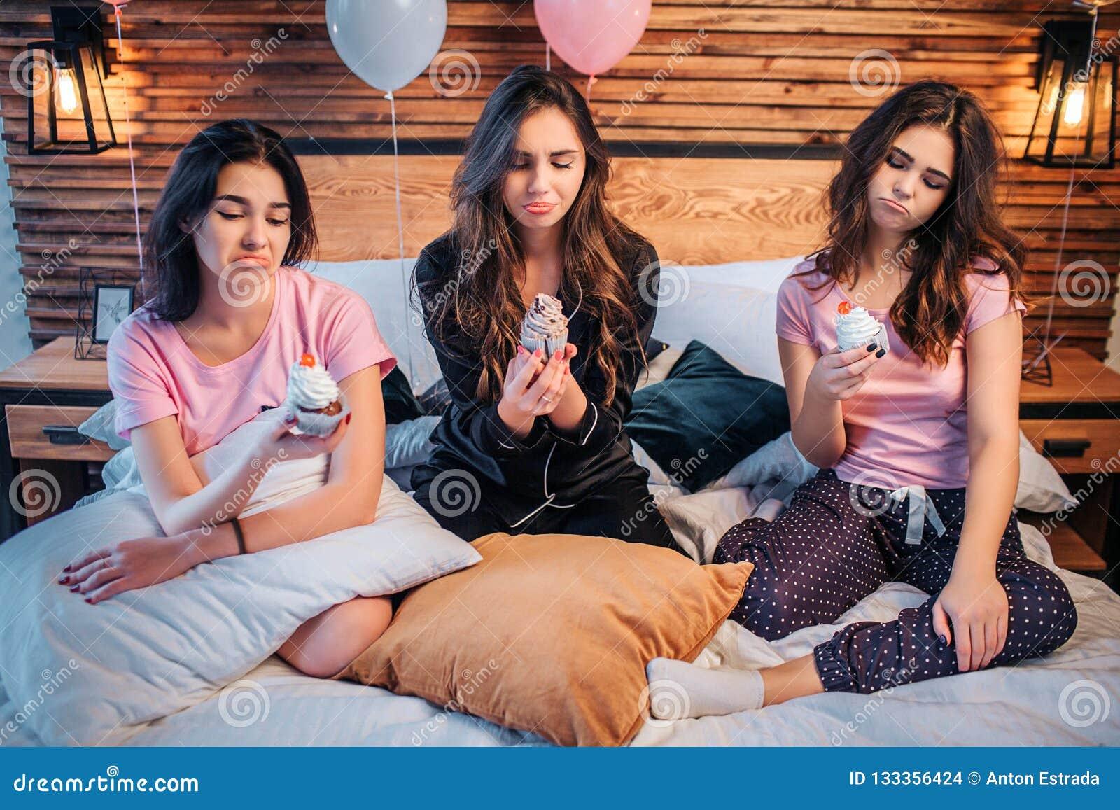 De droevige en verstoorde jonge vrouwen zitten op bed in ruimte Zij houden cakes en bekijken hen De jonge vrouwen zijn ongelukkig