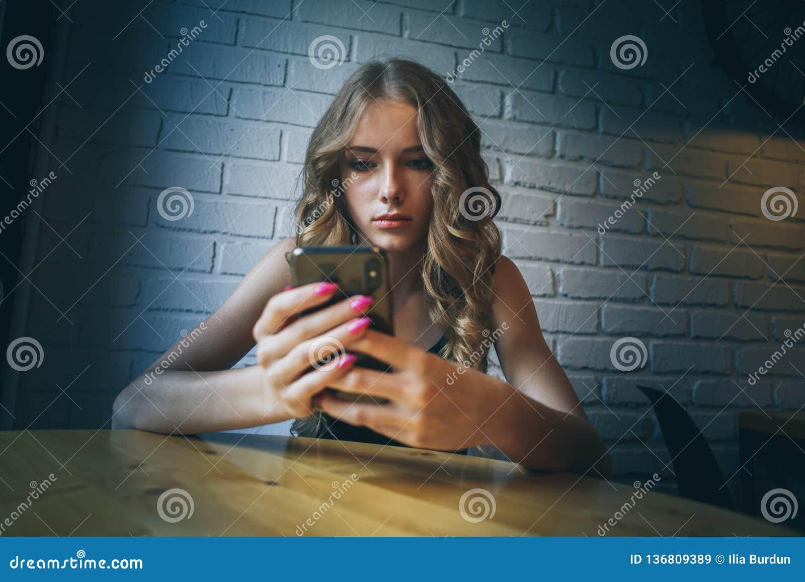 De droevige jonge meisjeszitting in een koffie die vermoeide haar telefoon, ongelukkig meisje die op haar zwarte telefoon letten