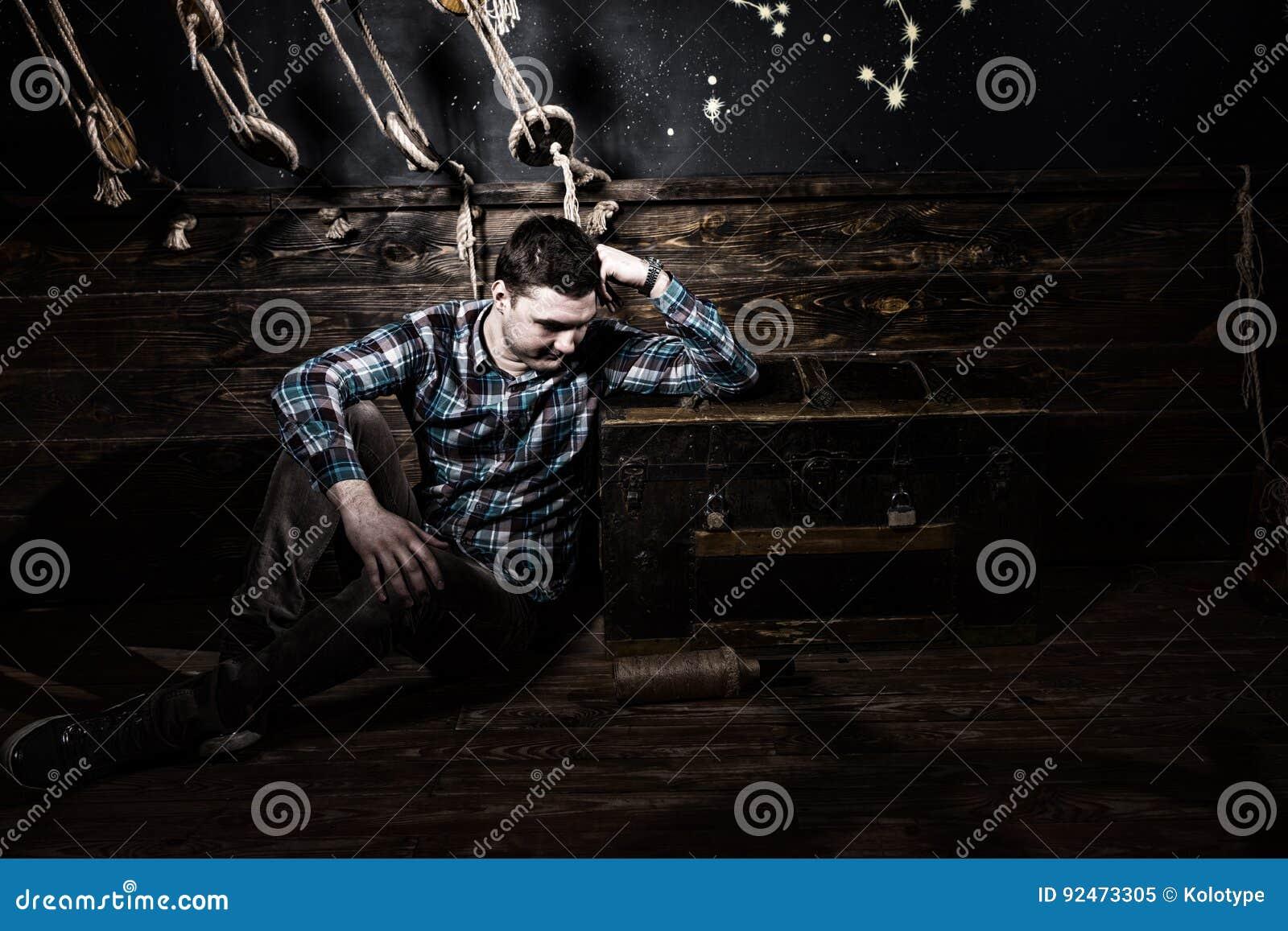 De droevige kerel zit dichtbij een borst die, die glasfles houden en aan Duitsland proberen