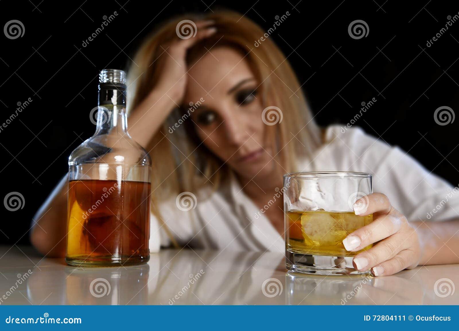 De dronken alcoholische vrouw verspilde en drukte het glas van de holdings Schotse whisky kijkend in nadenkend aan fles
