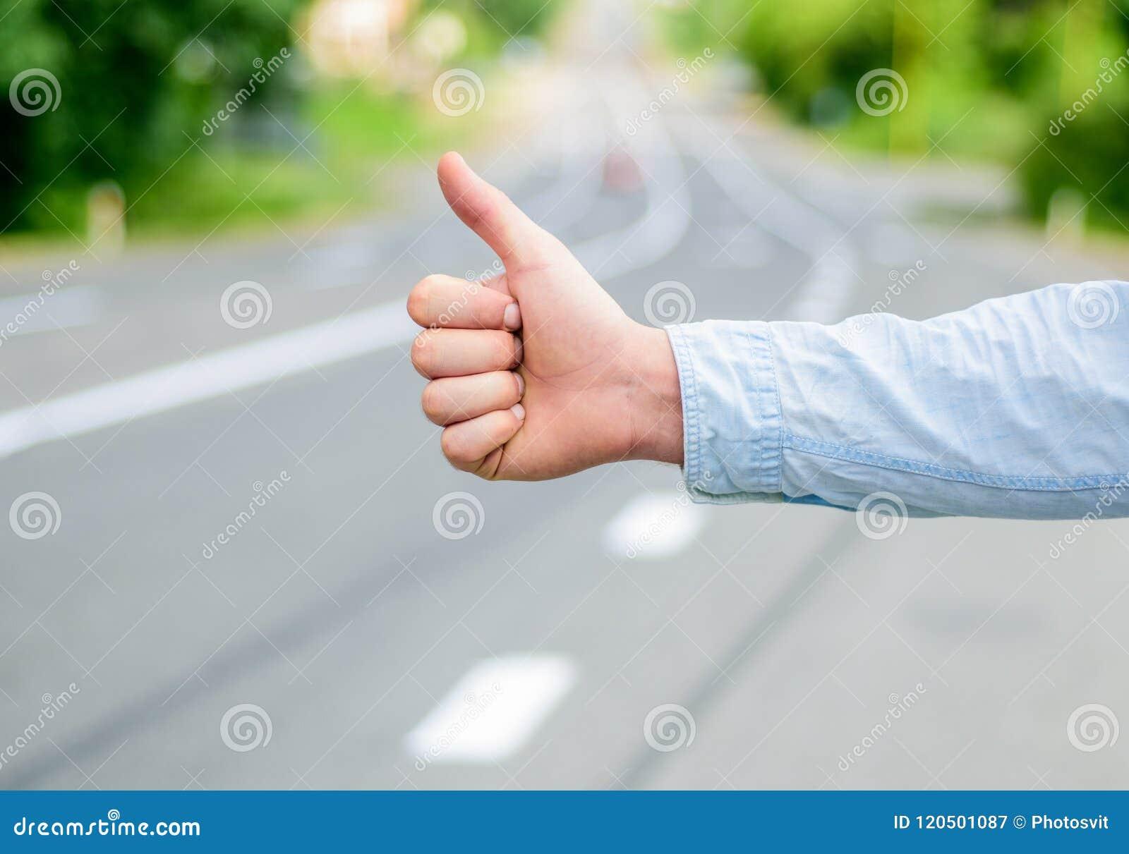 De duim op gebaar probeert de wegachtergrond van de eindeauto Handgebaar lift Zorg ervoor u juiste gebaren kent om auto tegen te