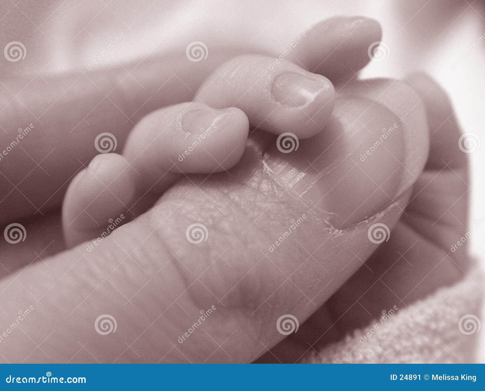 De duim van de holdingsdames van de baby