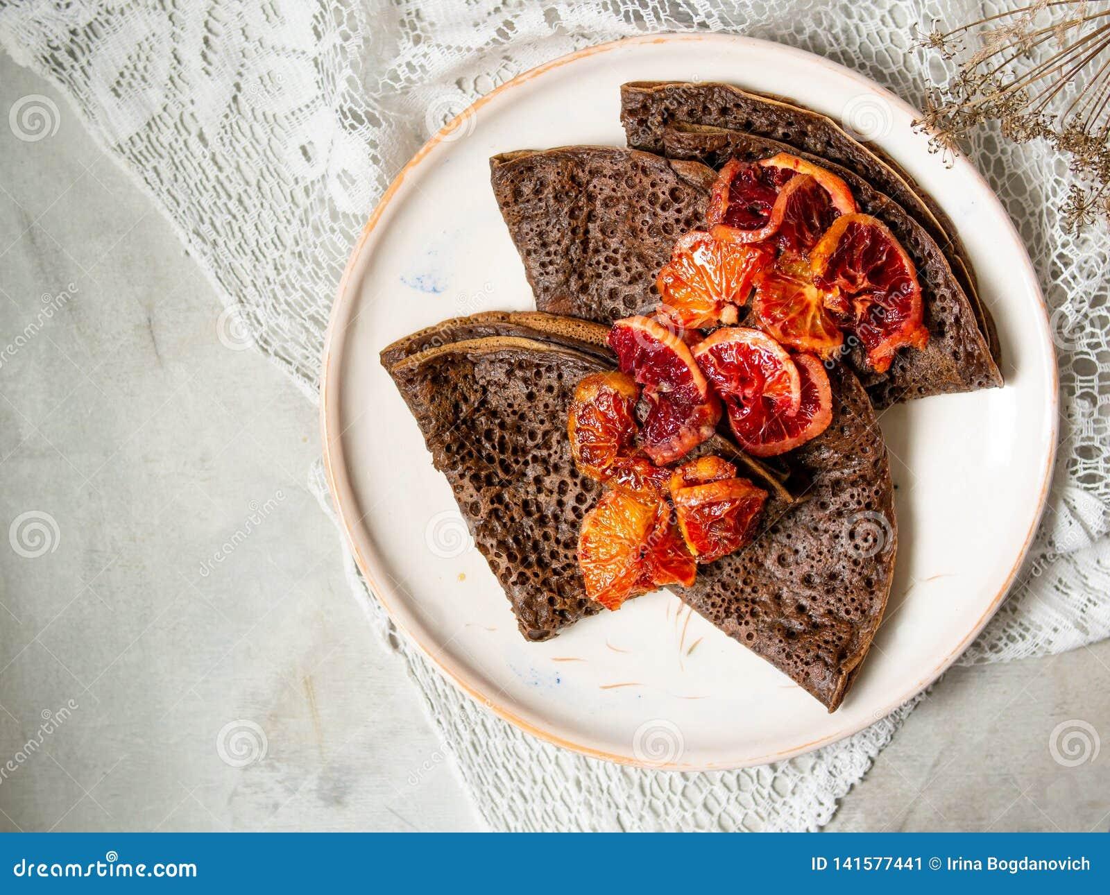De dunne chocoladepannekoeken met de saus van bloedsinaasappelen op een wit plateren op grijze achtergrond met kantstof De stapel