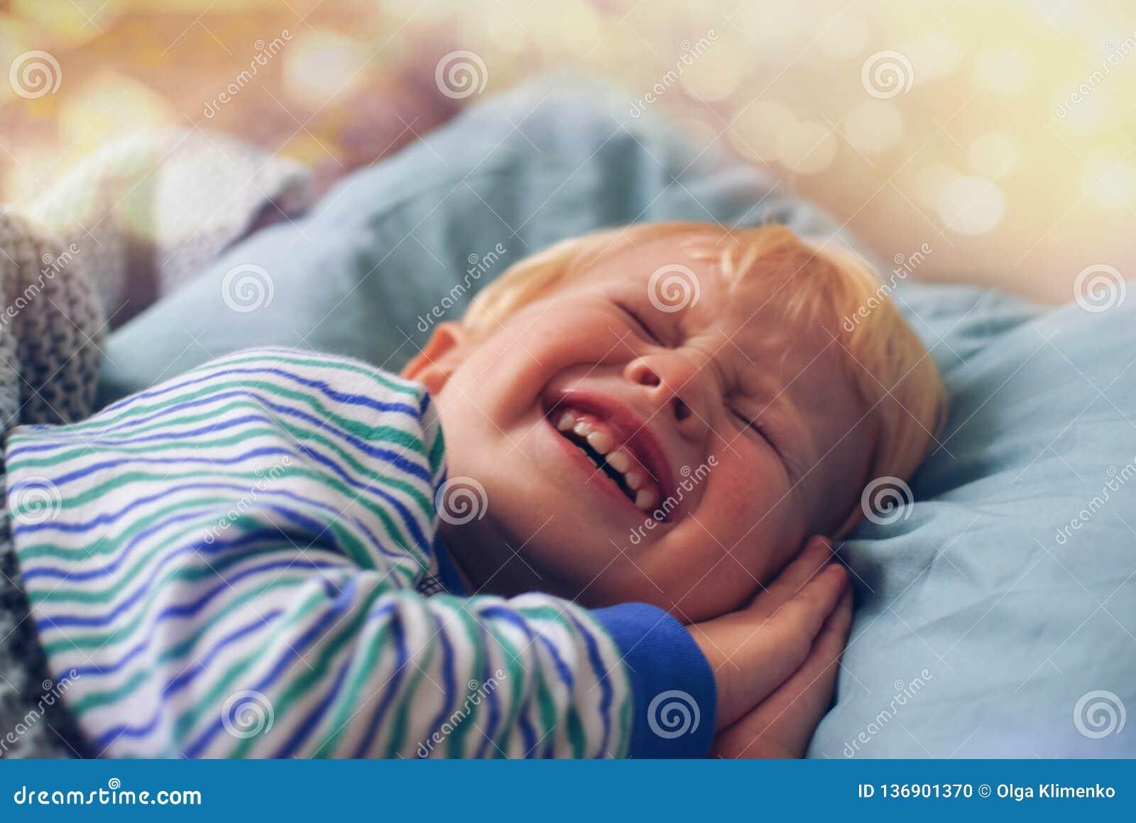 De een weinig blonde jongen in gestreepte pyjama s met zijn handen onder zijn wang knippert, proberend aan slaap