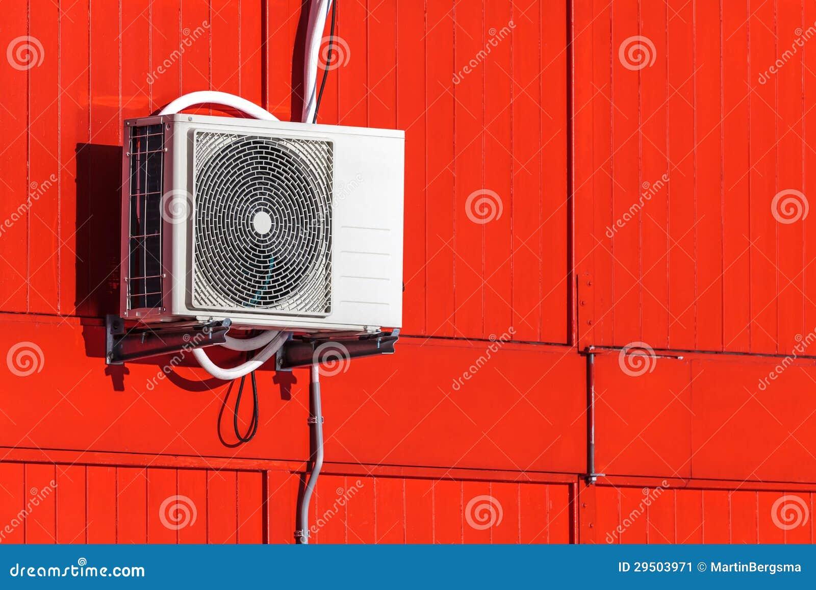 De eenheid van de airconditioning op een rode muur