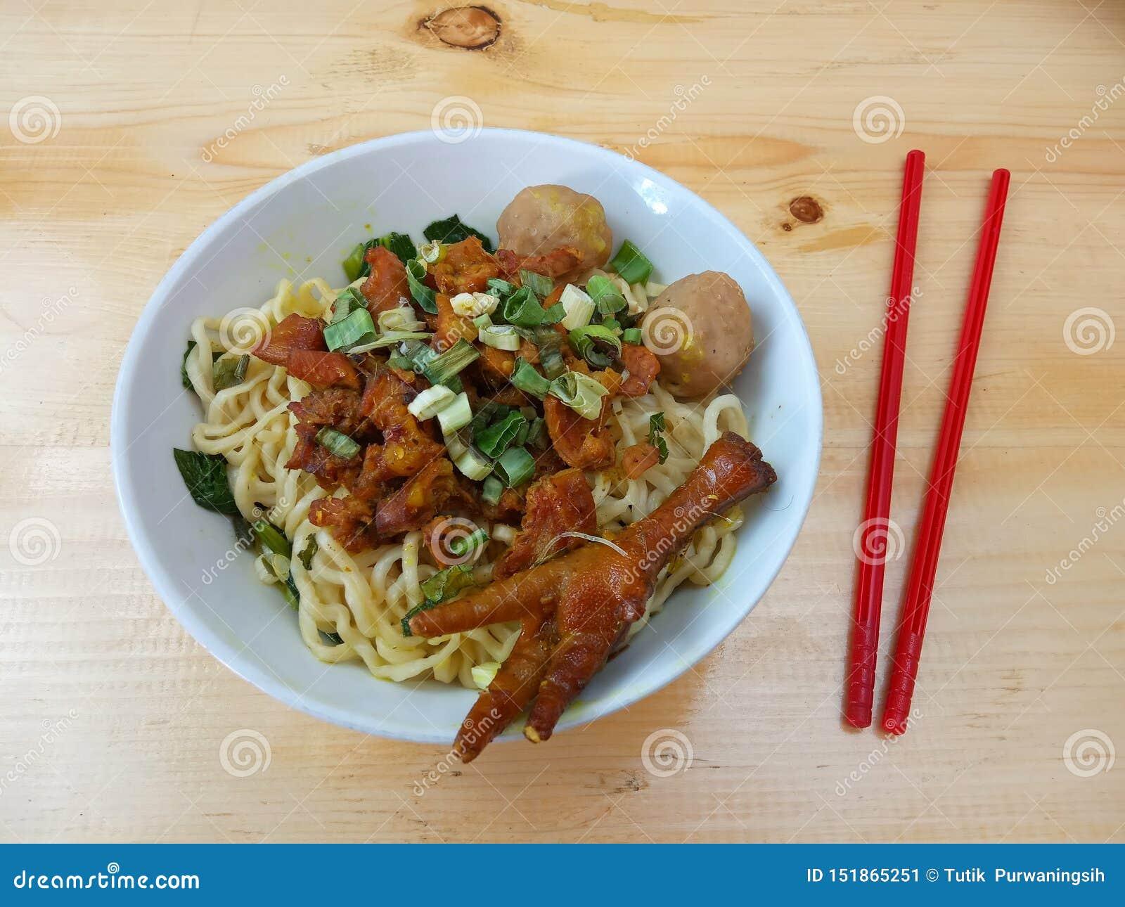 De eenvoudige Vlakke Foto, legt, heerlijke bakso van Mie Ayam ceker, Kippennoedel bij witte kom en rood plastic eetstokje bij hou