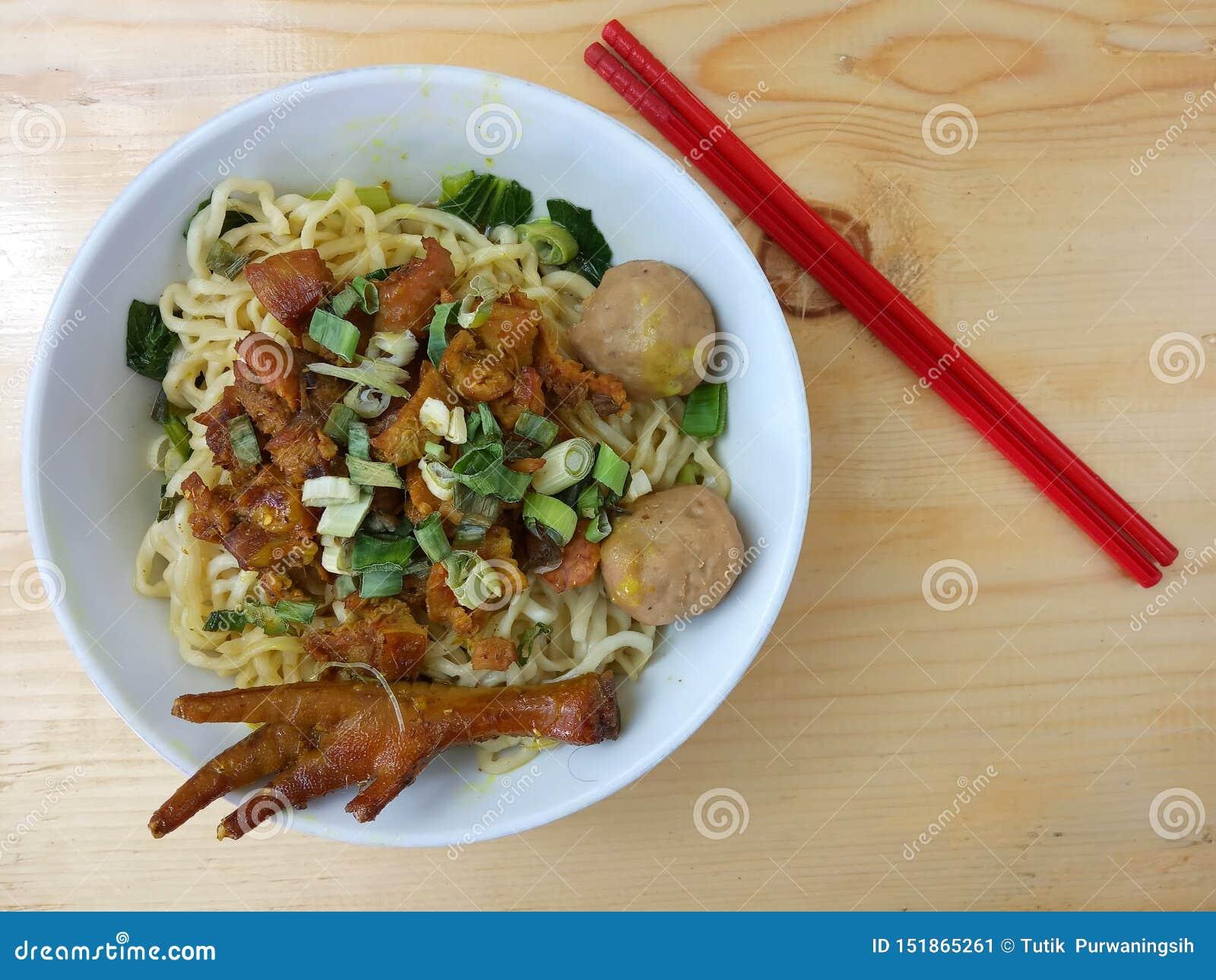 De eenvoudige Vlakke Foto, legt, heerlijke Mie Ayam, Kippennoedel bij witte kom en rood plastic eetstokje bij houten lijst van In