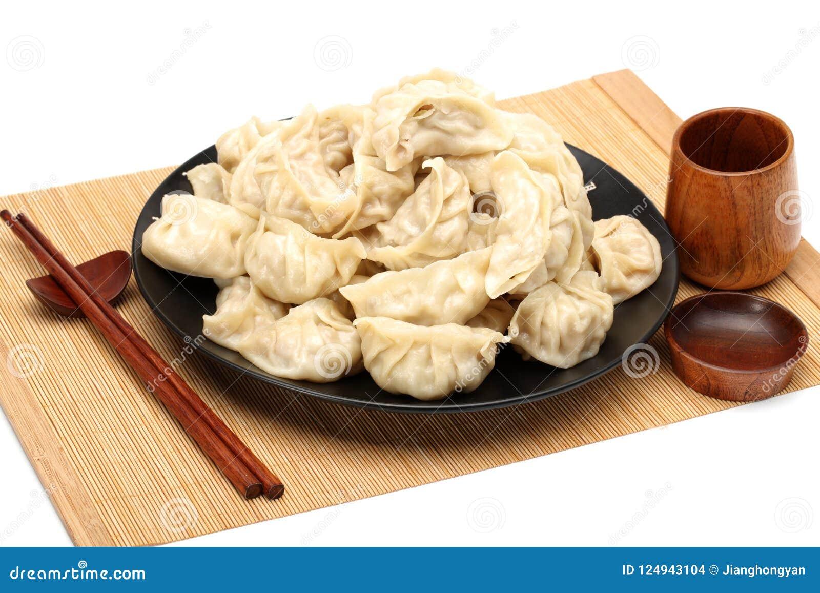 De eetstokjes nemen de Bollen van Boilded Chineses van een Plaat op De Bol, genoemd Jiaozi in Chinees, is een populaire tradition