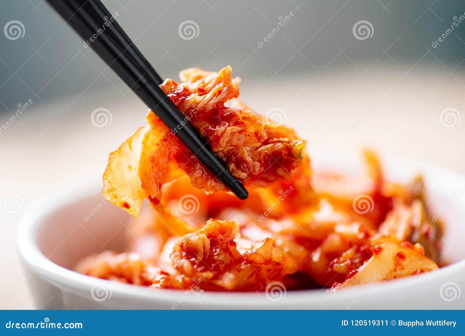 De eetstokjes van de handholding voor het eten van kimchikool