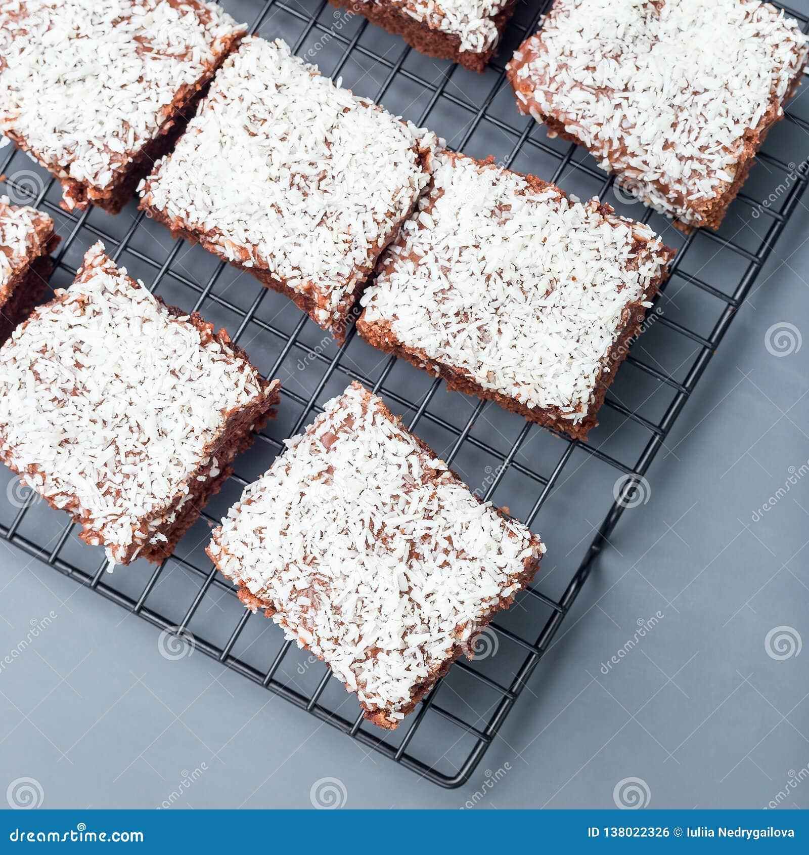 De eigengemaakte brownie met kokosnoot schilfert, Zweeds dessert Karleksmums, besnoeiing in vierkante porties, bij het koelen van