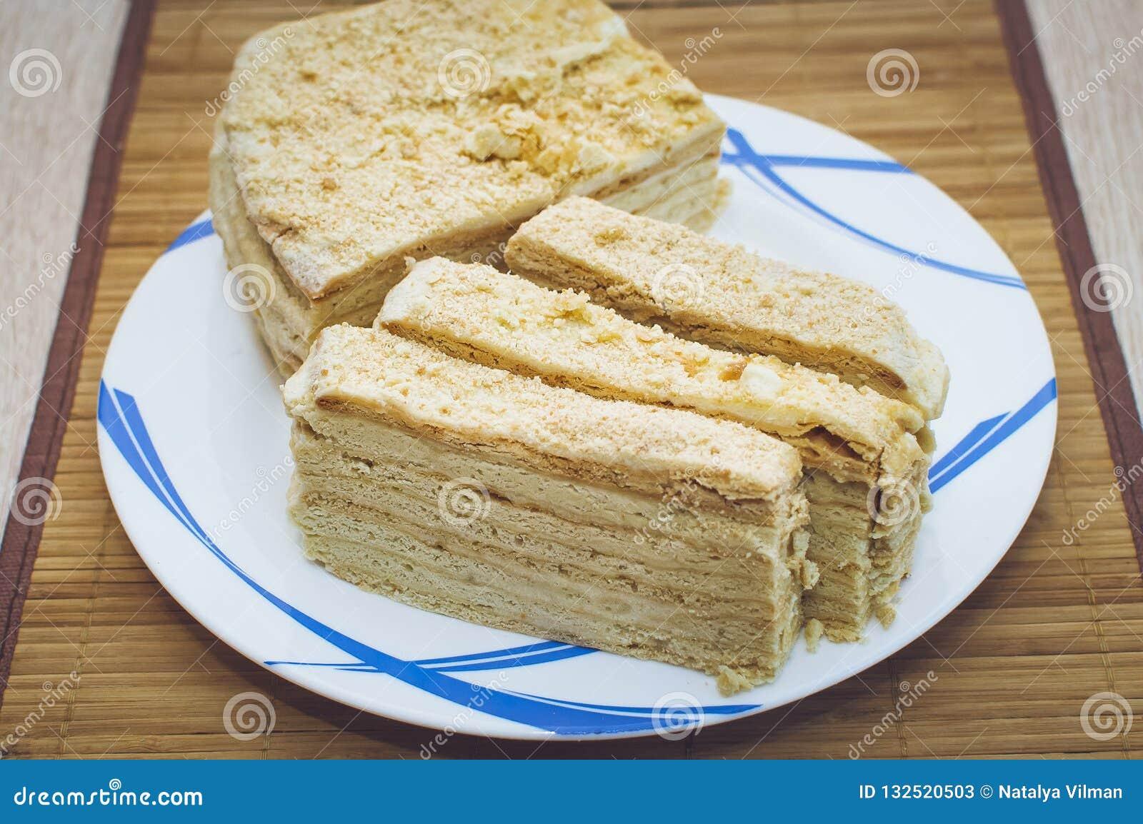 De eigengemaakte honingscake ligt op een plaat op een bamboeservet Close-up, selectieve nadruk