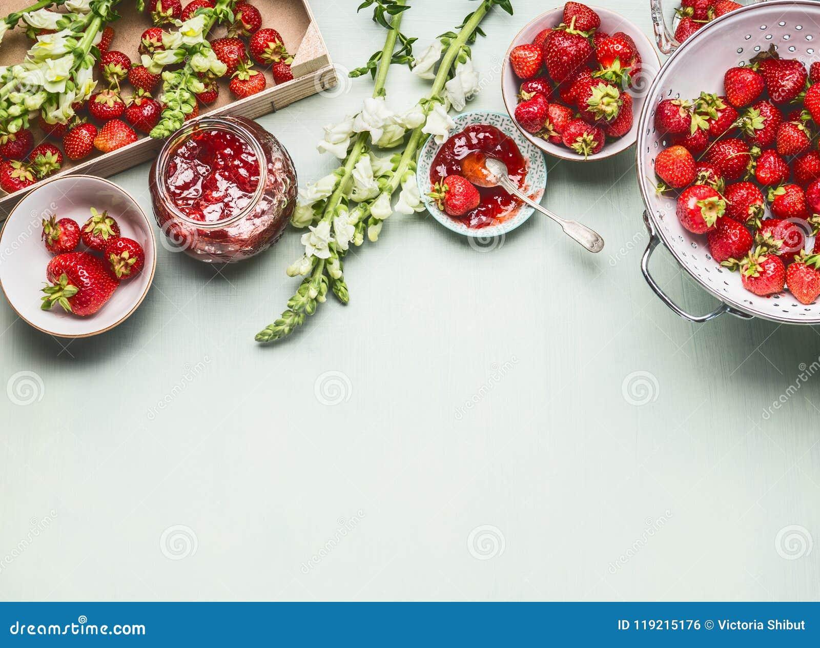 De eigengemaakte smakelijke aardbeienjam in glaskruik met de zomer bloeit en verse bessen, kommen en lepel op lijstachtergrond, h