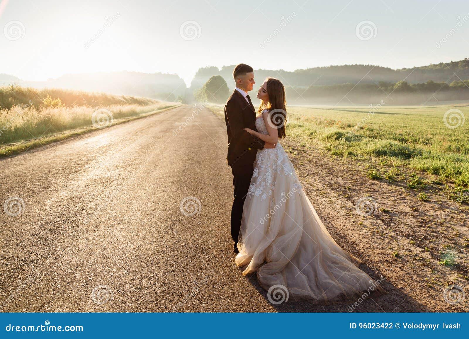 De elegante die tribunes van het huwelijkspaar op de weg worden vermoeid