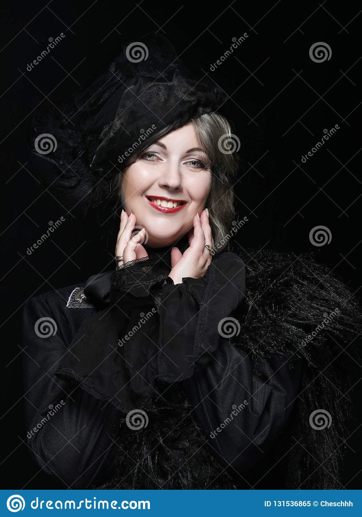 De elegante vrouw op middelbare leeftijd in een zwarte hoed met een sluier en een luxe kleden zich