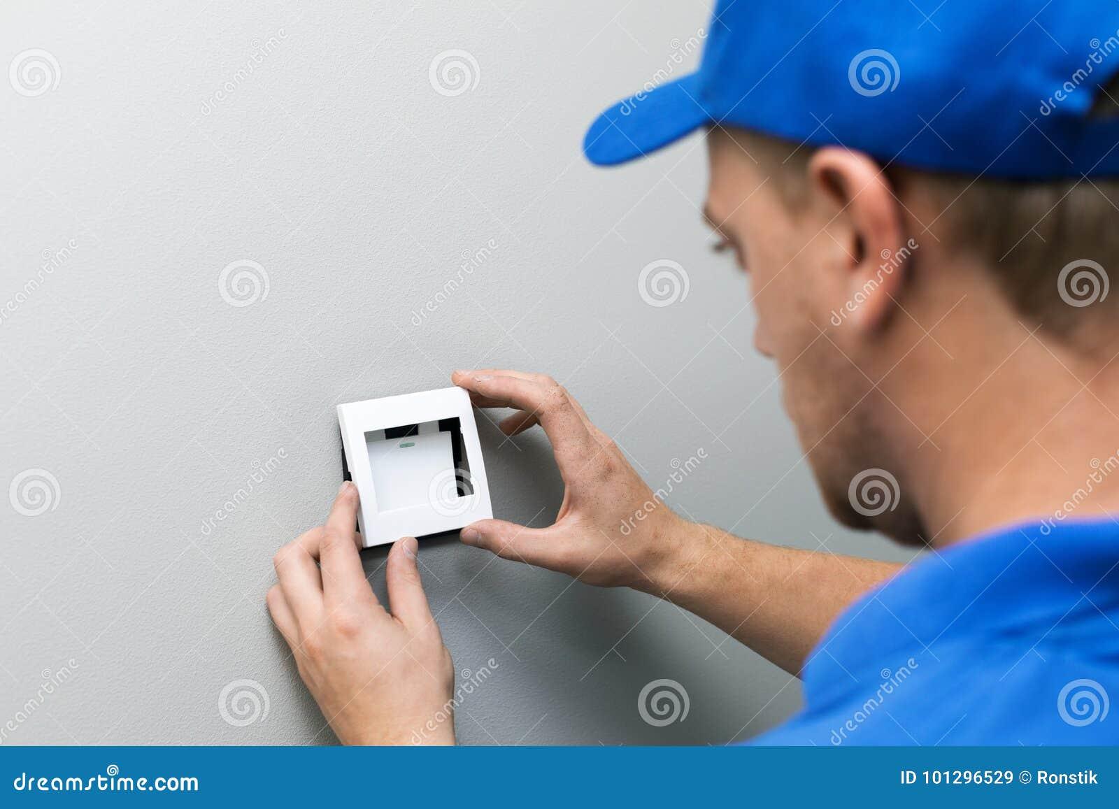 De elektricien die licht installeren schakelt de muur in