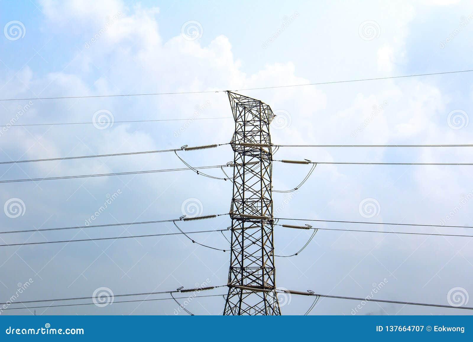 De elektrische lijnen van de hoogspanningsmacht, tegen een blauwe hemel