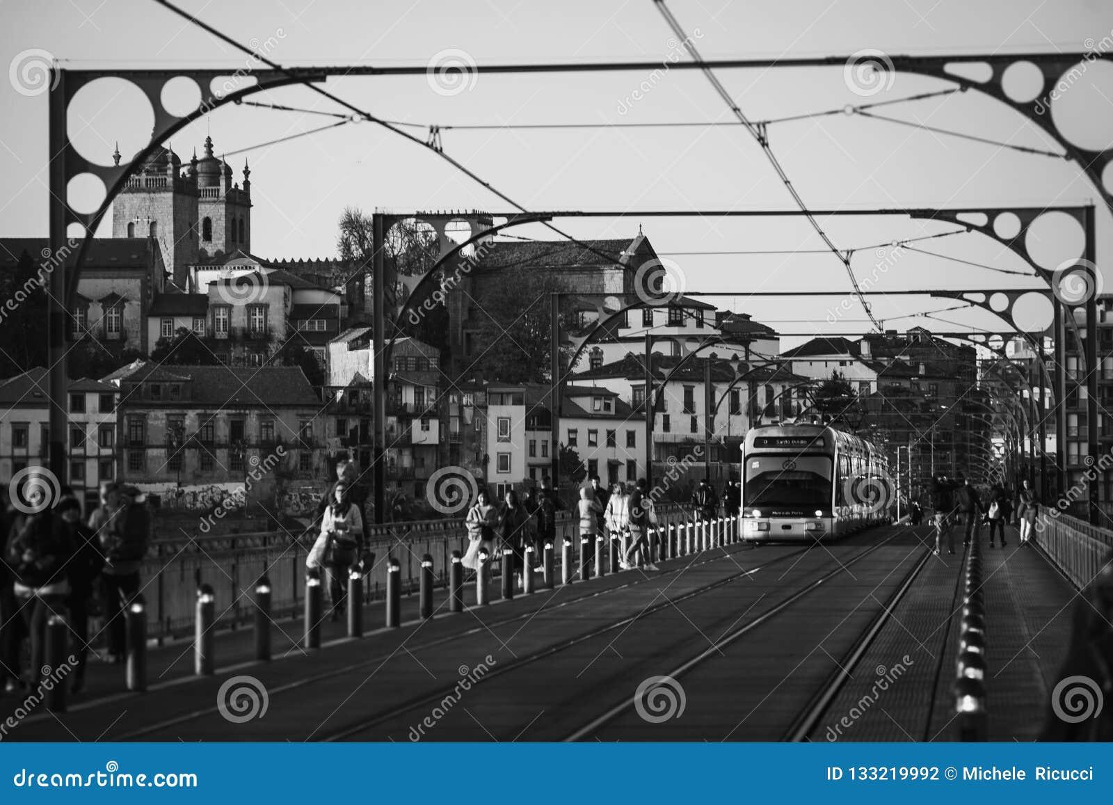 De elektrotram over dom luis overbrugt in porto stad van Portugal in zwart-wit