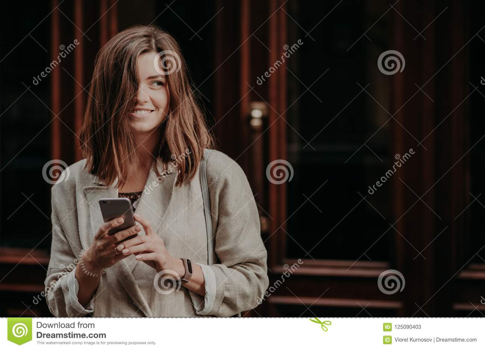 De emotionele opgetogen gelukkige donkerbruine jonge vrouw met donker haar, gebruiks mobiele telefoon voor het texting van berich